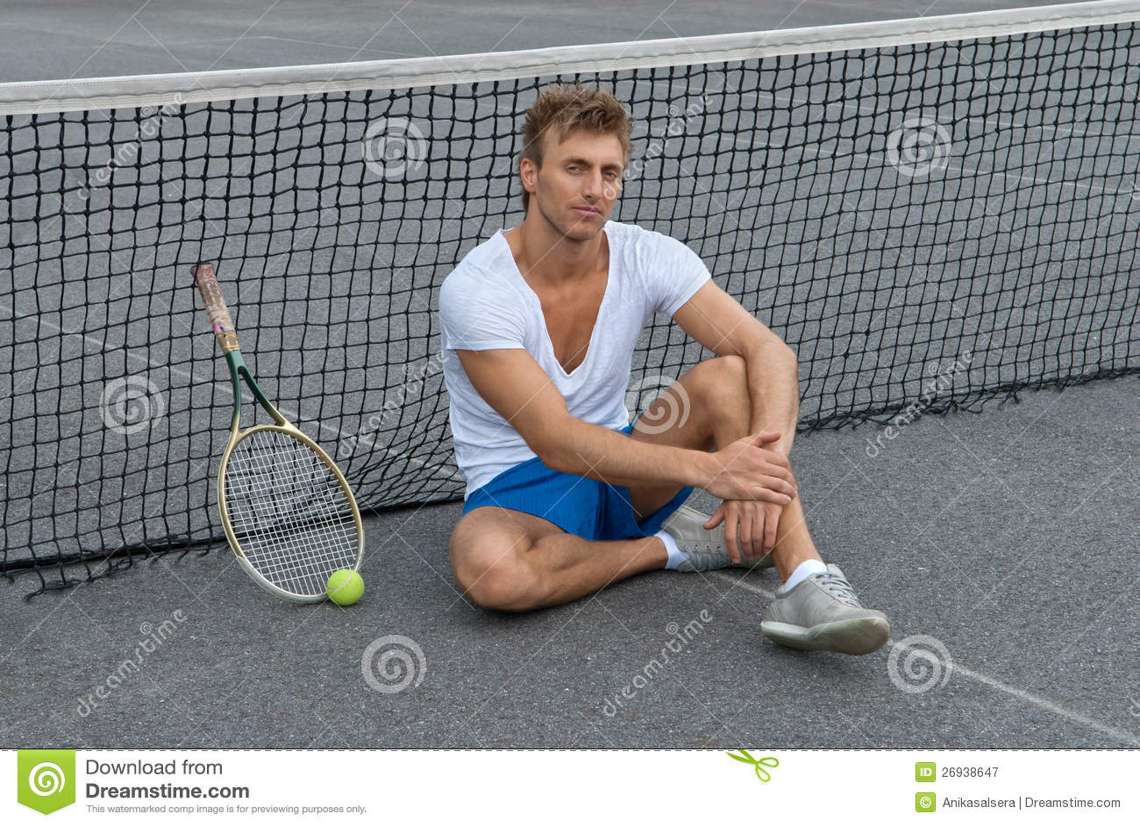 Sentada del jugador de tenis además de la red
