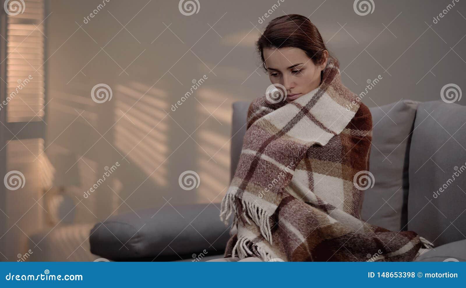 Sentada femenina deprimida sola en el sof?, cubierto con la tela escocesa, desempleo