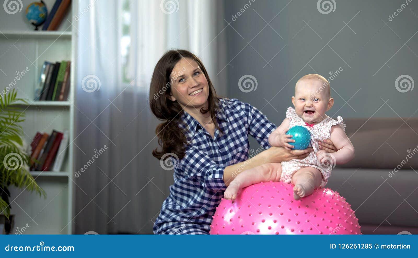 Sentada infantil adorable en bola y risa, bebé que se divierte con la madre cariñosa
