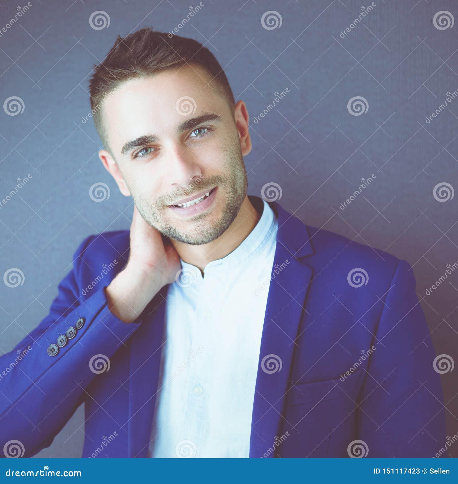 Sentada joven del hombre de negocios aislada en fondo gris