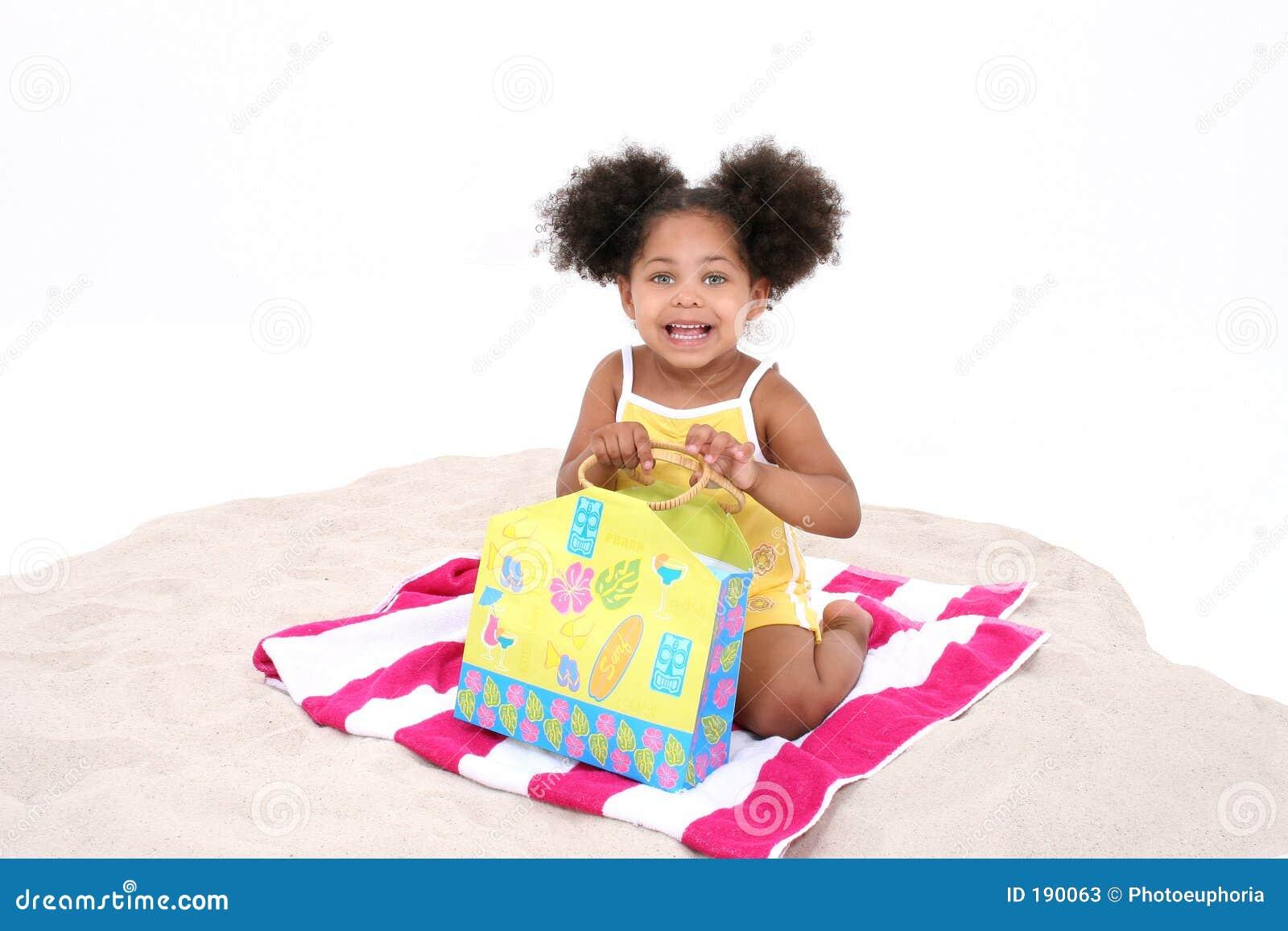 Sentada joven hermosa en la arena