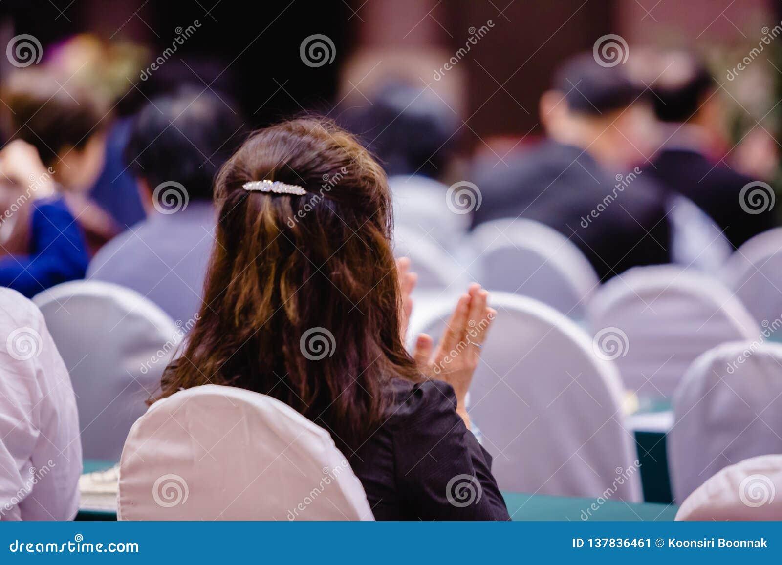 Sentada y palmada de la mujer de negocios en el auditorio para reunión de los accionistas '