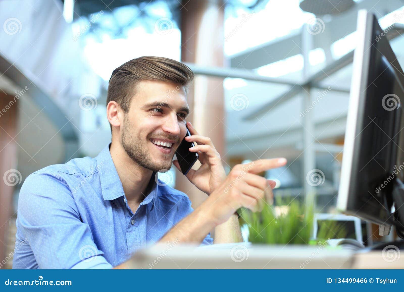 Sentada y usar sonrientes del hombre de negocios el teléfono móvil en oficina