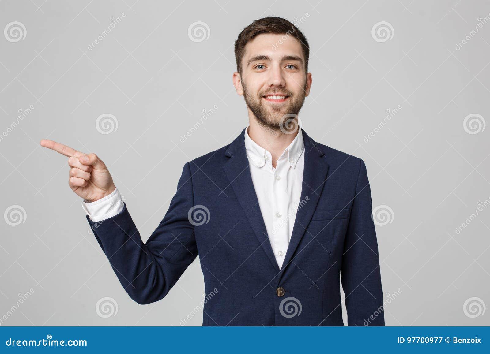Sentido apontando do homem de negócios bem sucedido novo com o dedo sobre o fundo cinzento escuro Copie o espaço