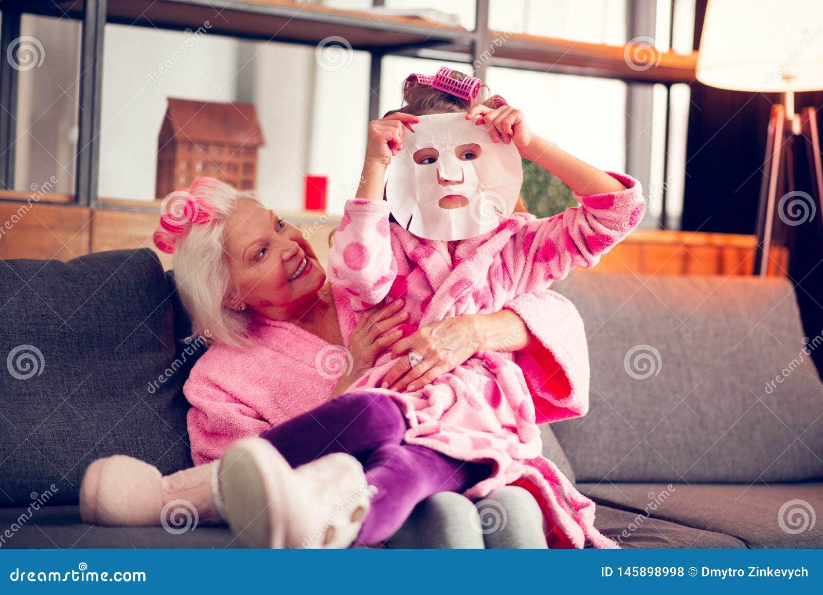 Sentimento da menina curioso ao tentar a máscara da folha no assento perto da avó