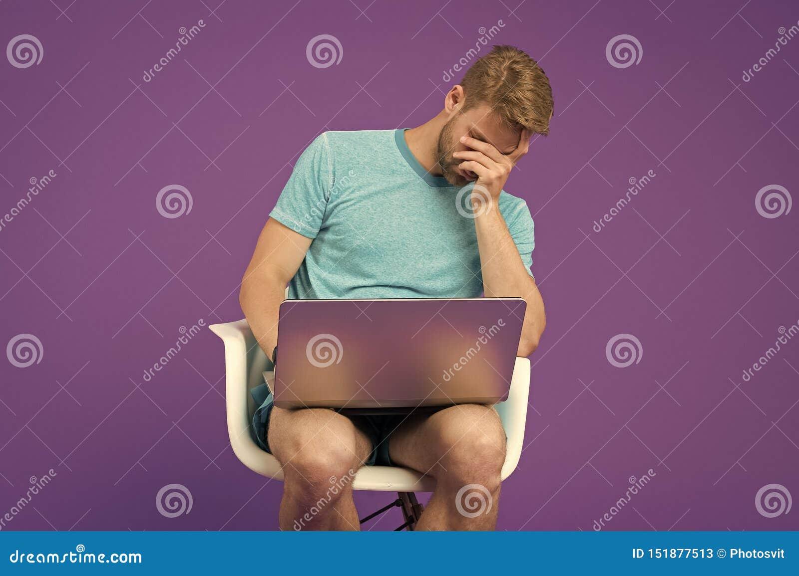 Sentimento doente e cansado Cara frustrante da coberta do homem novo com m?os ao sentar-se com port?til Internet surfando do home