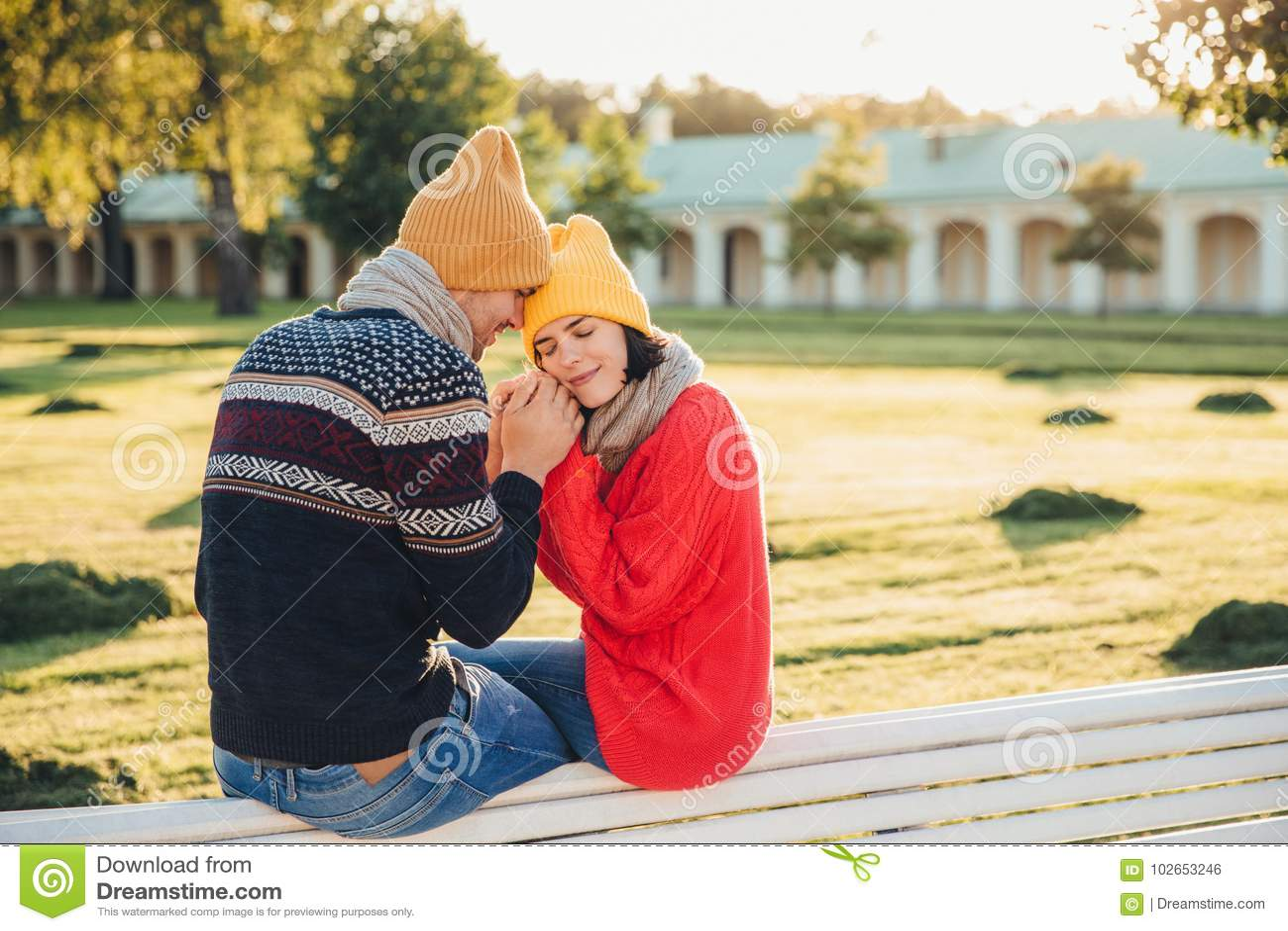 Sentimentos e conceito verdadeiros do romantisism A jovem mulher adorável no chapéu amarelo feito malha e na camiseta morna verme