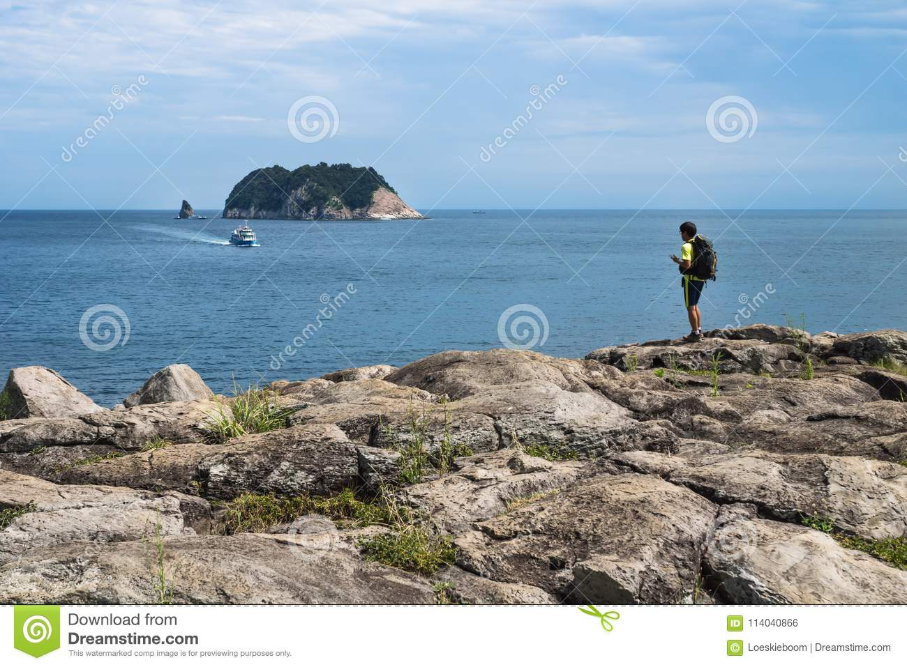 Hiker on the cliff of Seogwipo looking to boat and Moon Island, Jeju Island, South Kodrea
