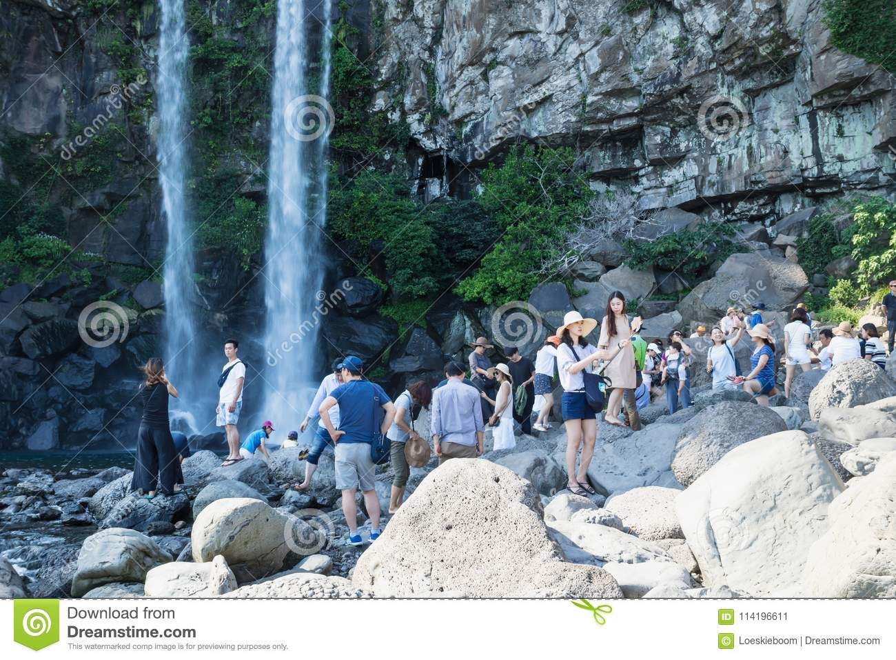 Tourists making pictures at the Jeongbang waterfall in Seogwipo, Jeju Island, South Korea