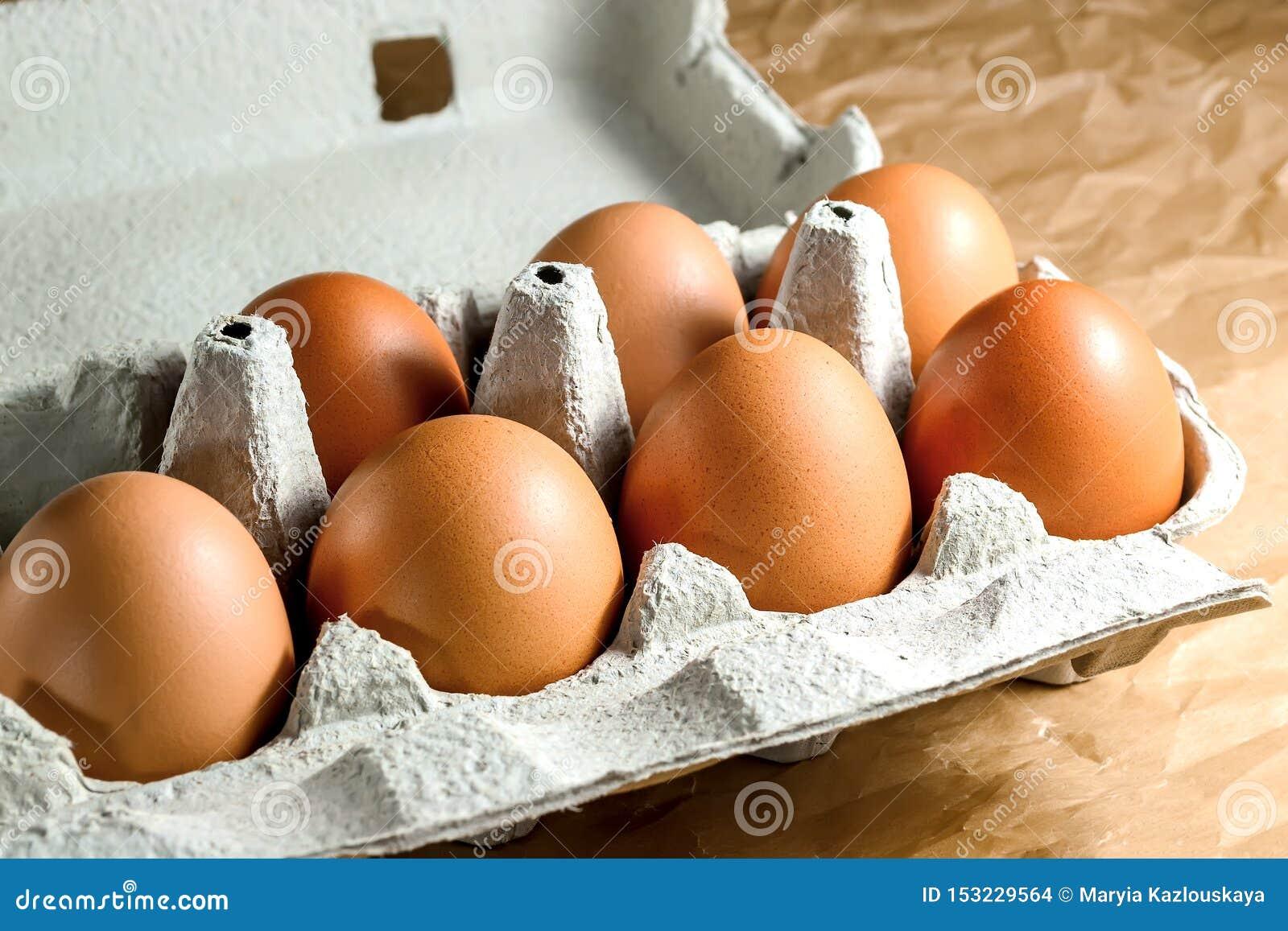 Sept oeufs bruns de poulet dans un emballage de papier de carton sur une table de cuisine Oeufs pour la consommation saine de bre
