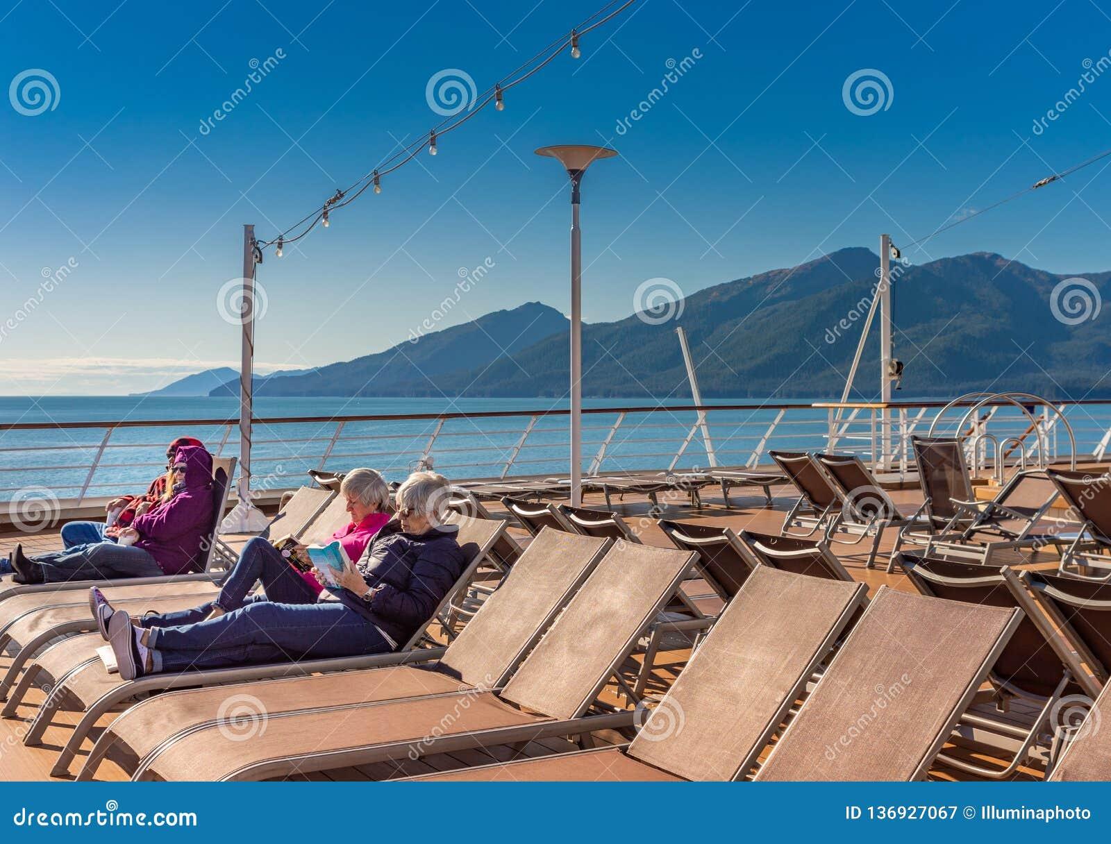 September 14, 2018 - Inside Passage, Alaska: Cruise passengers reading outdoors.