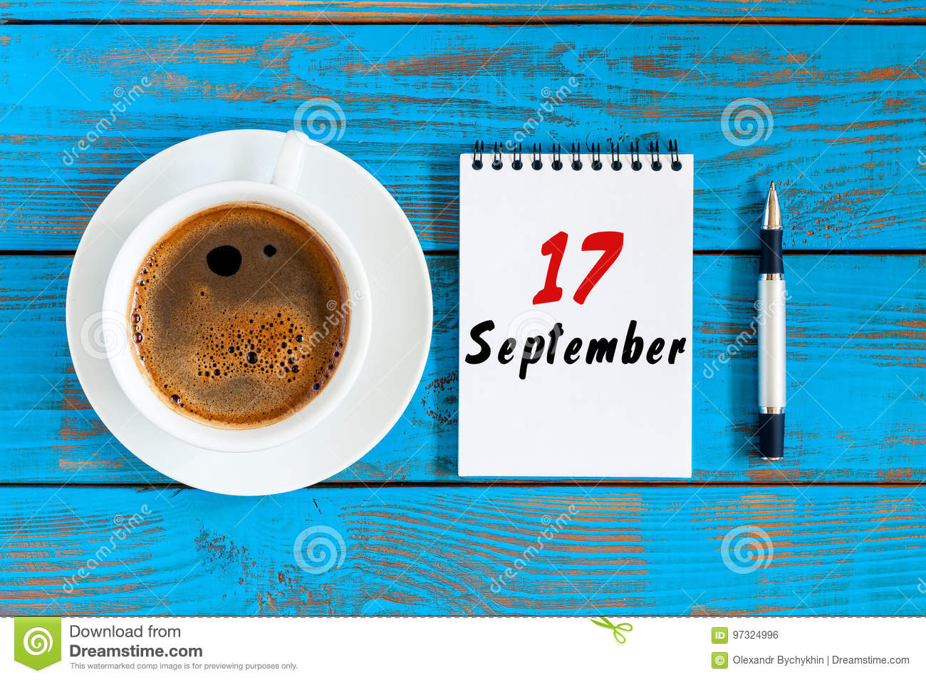 September 17th. Day 17 of month, loose-leaf calendar and coffee cup at Network Systems Analyst workplace background