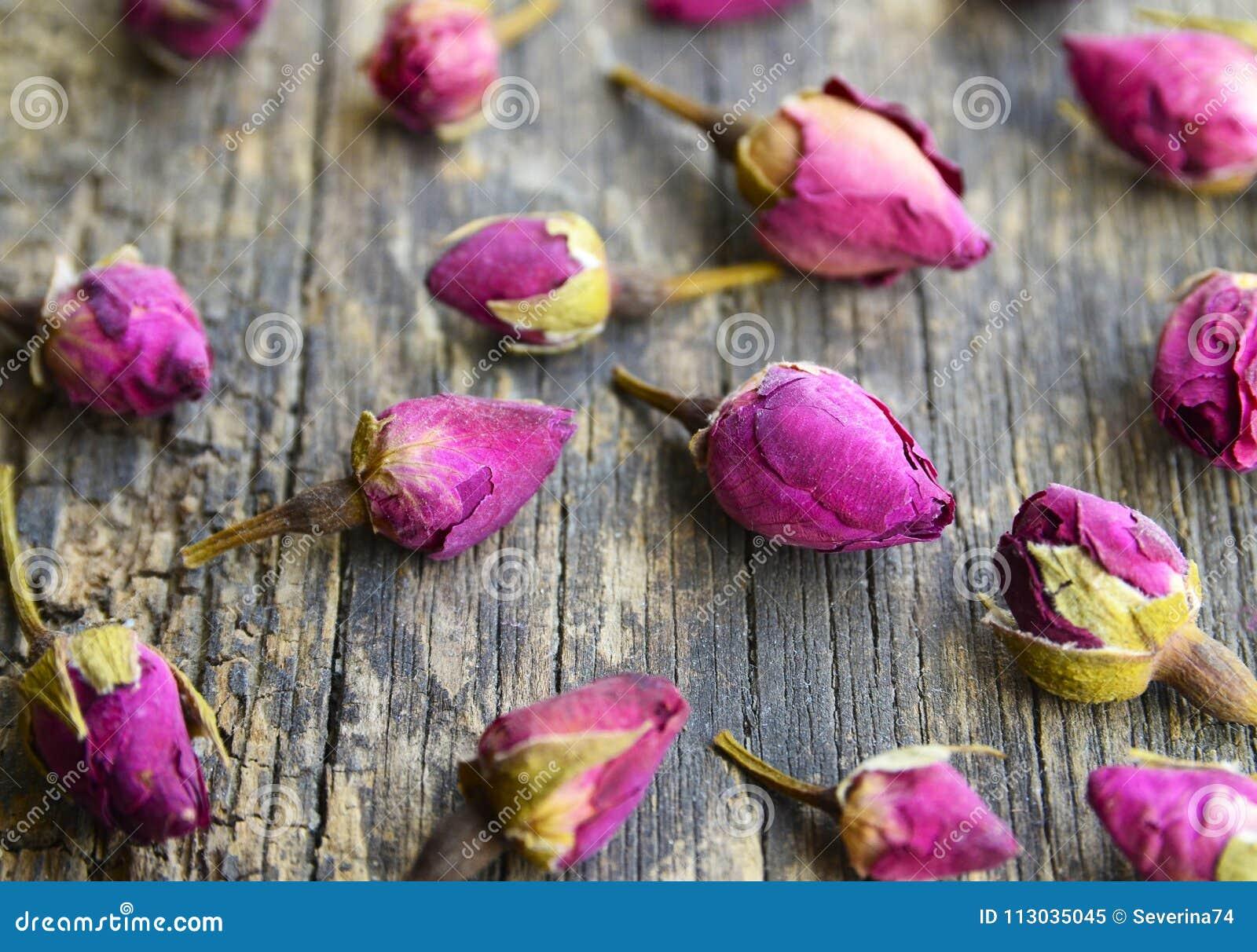 Seque las flores color de rosa de los brotes en la tabla de madera vieja Ingrediente asiático para la infusión de hierbas del aro