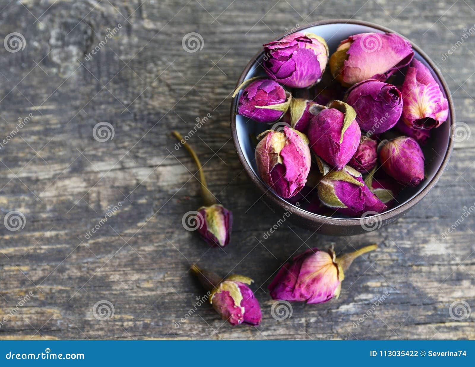Seque las flores color de rosa de los brotes en un cuenco en la tabla de madera vieja Concepto herbario sano de las bebidas Ingre