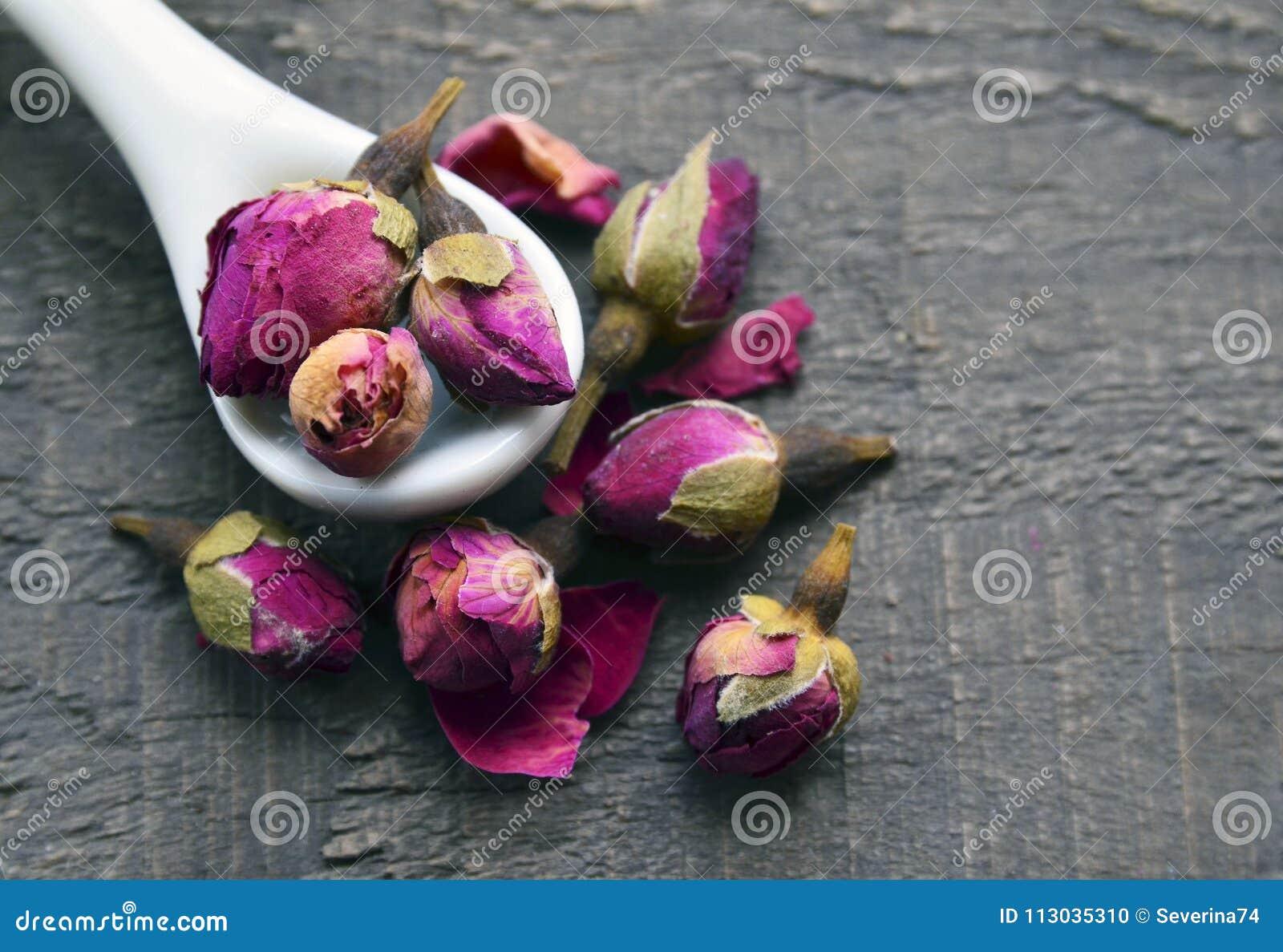 Seque las flores color de rosa de los brotes en una cuchara blanca en la tabla de madera vieja Ingrediente asiático para la infus