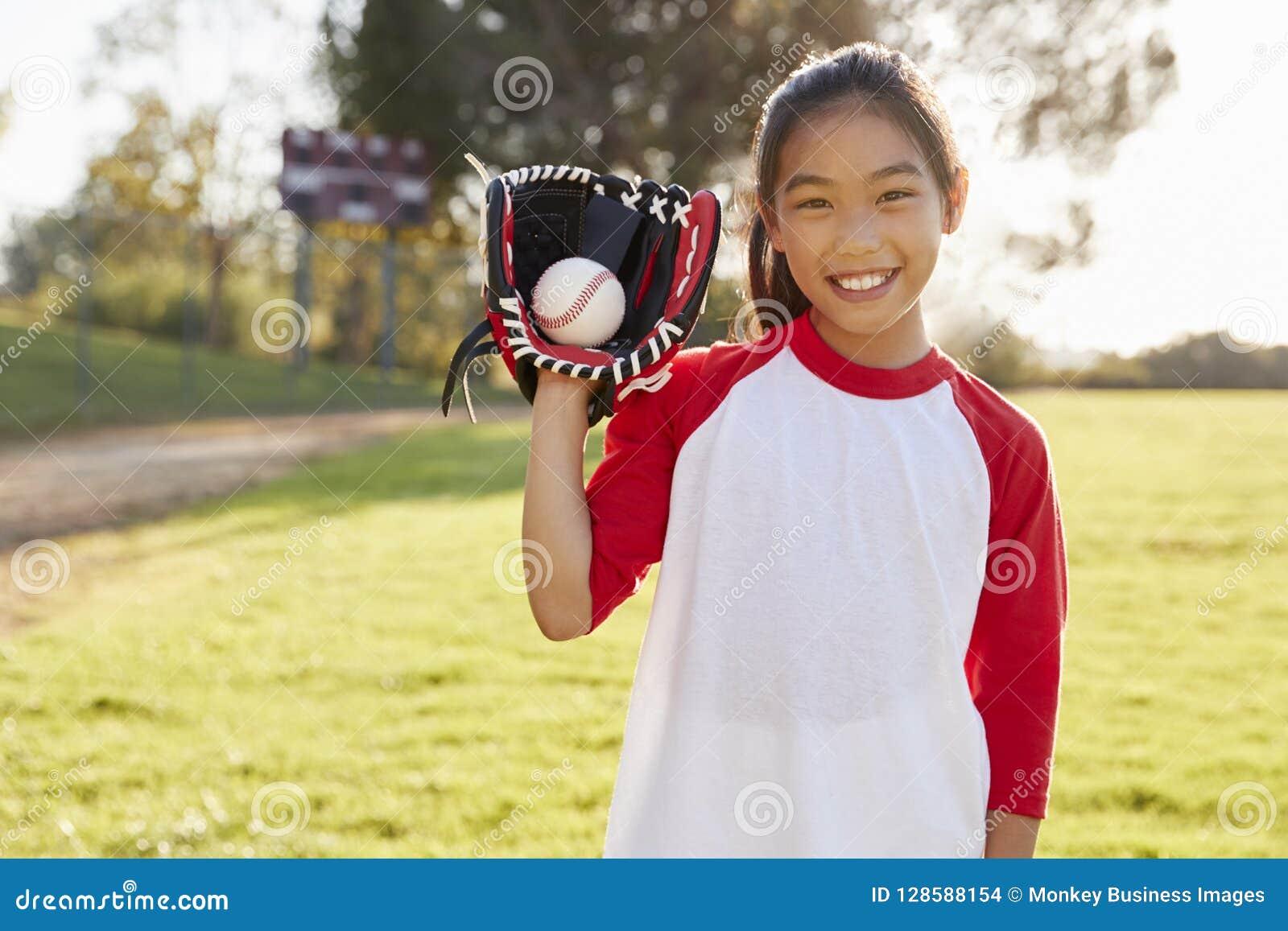 Ser hållande baseball för den unga kinesiska flickan i karda till kameran
