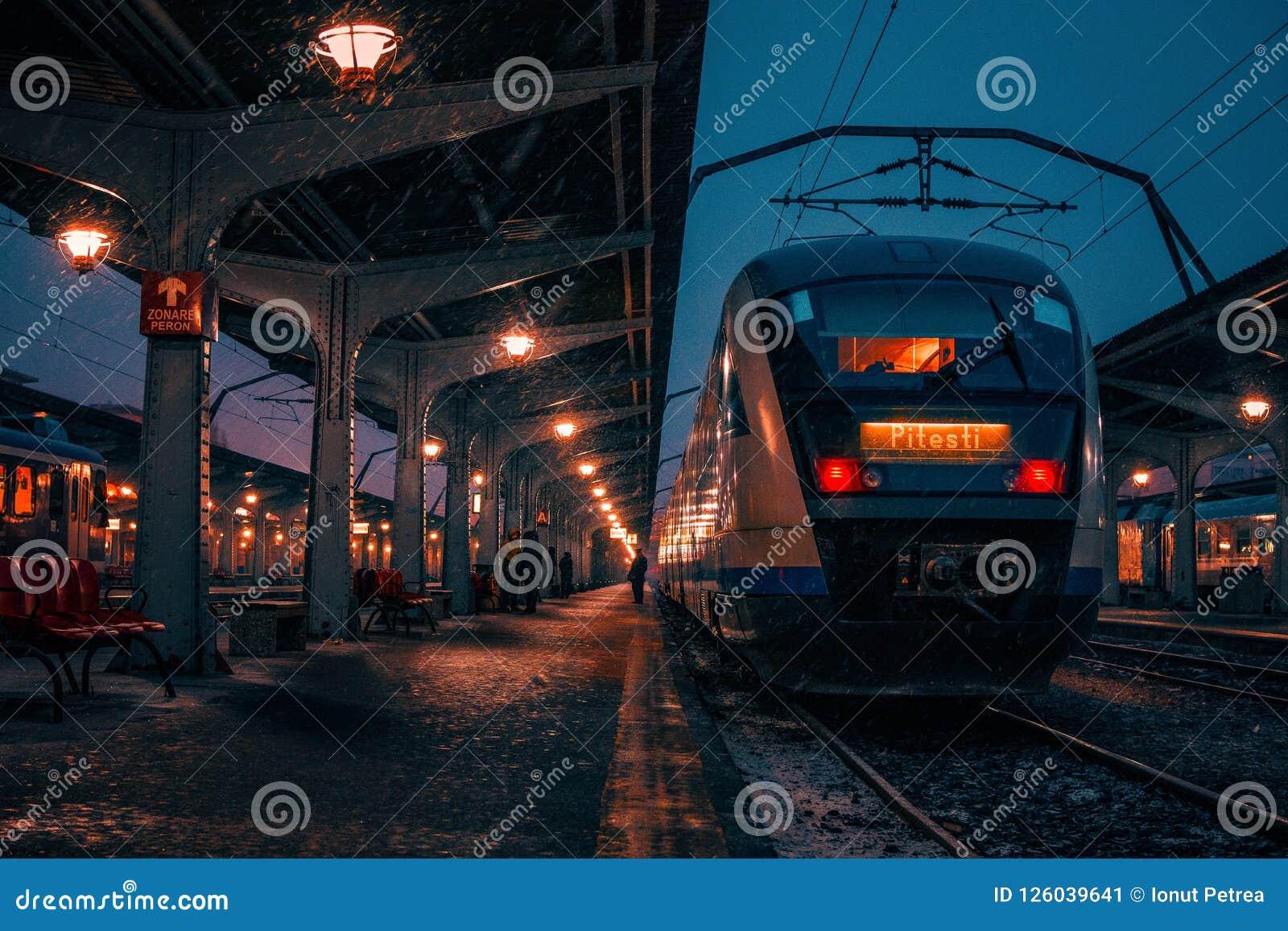 Ser humano na obscuridade em um estação de caminhos-de-ferro na plataforma durante um sn