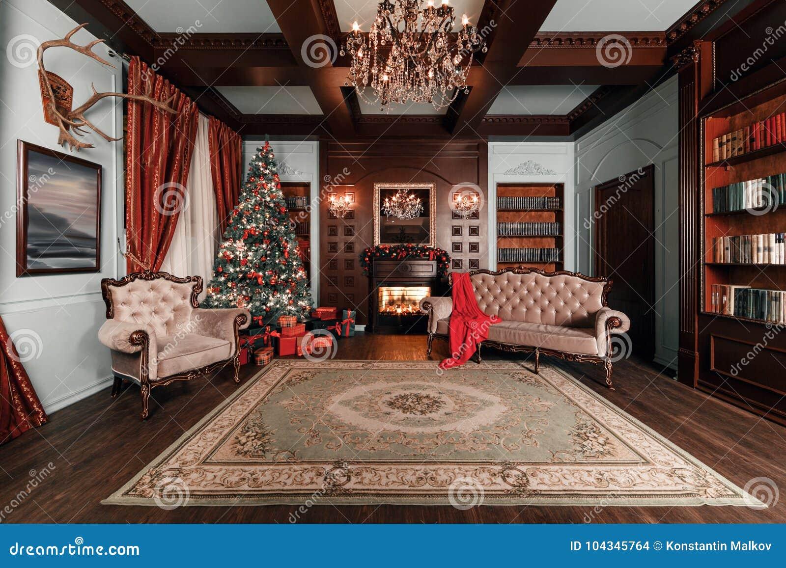 Sera di natale appartamenti classici con un camino bianco, un albero decorato, un sofà, le grandi finestre e un candeliere