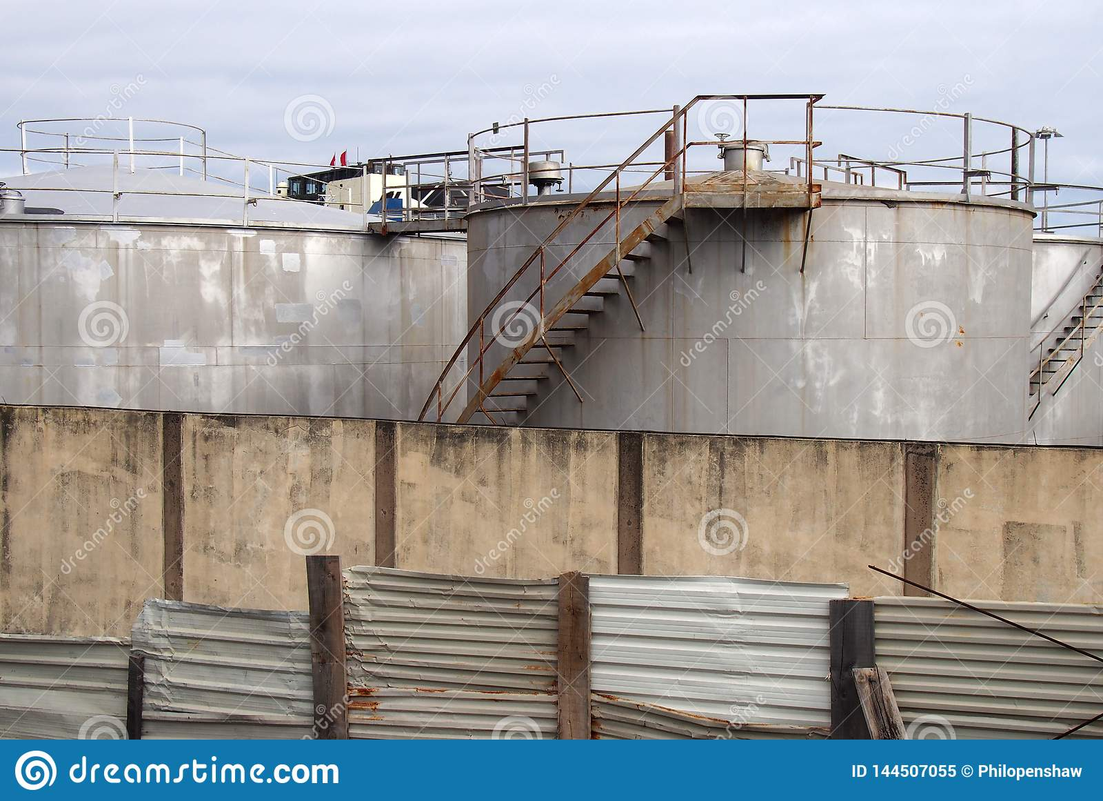 Serbatoi industriali del vecchio metallo con le scale arrugginite di ispezione e valvole circondate da un recinto e da una parete