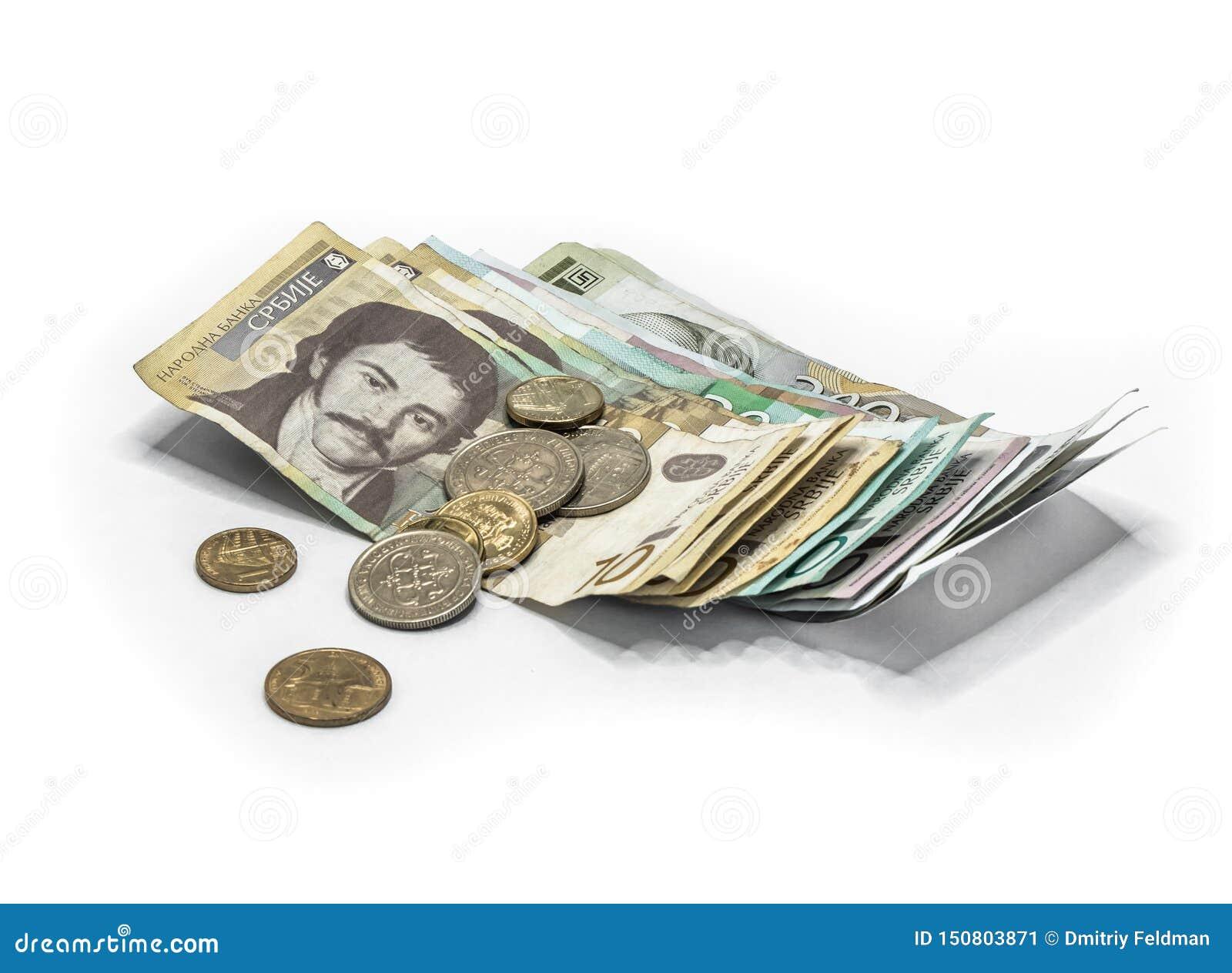 Serbisk pengarbunt av sedlar av olikt värde i serbiska dinar med olika mynt i serbiska dinar som isoleras på ett vitt b