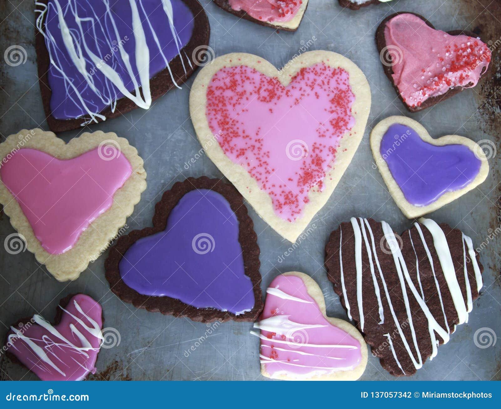 Serce Kształtował waniliowych, czekoladowych ciastka i różowym i purpurowym dla walentynka dnia na metalu ciastka prześcieradle z