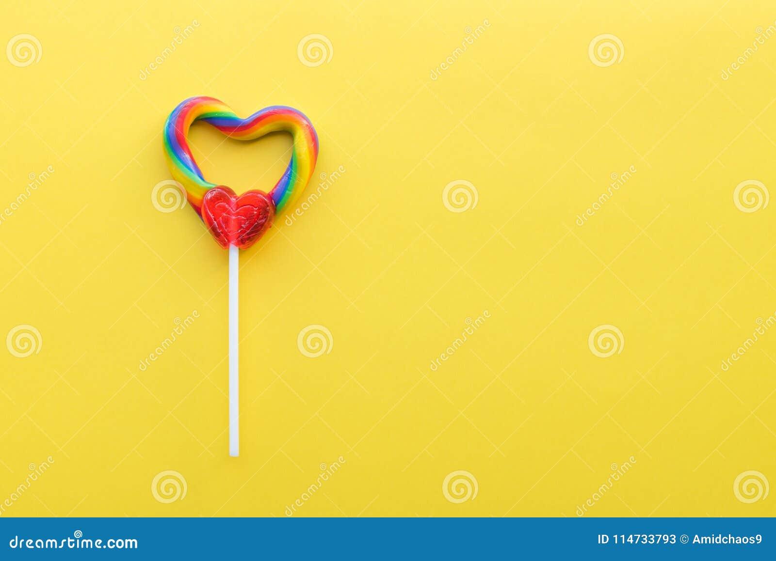Serce kształtujący tęcza zawijasa lizak na jaskrawym żółtym stałym tle