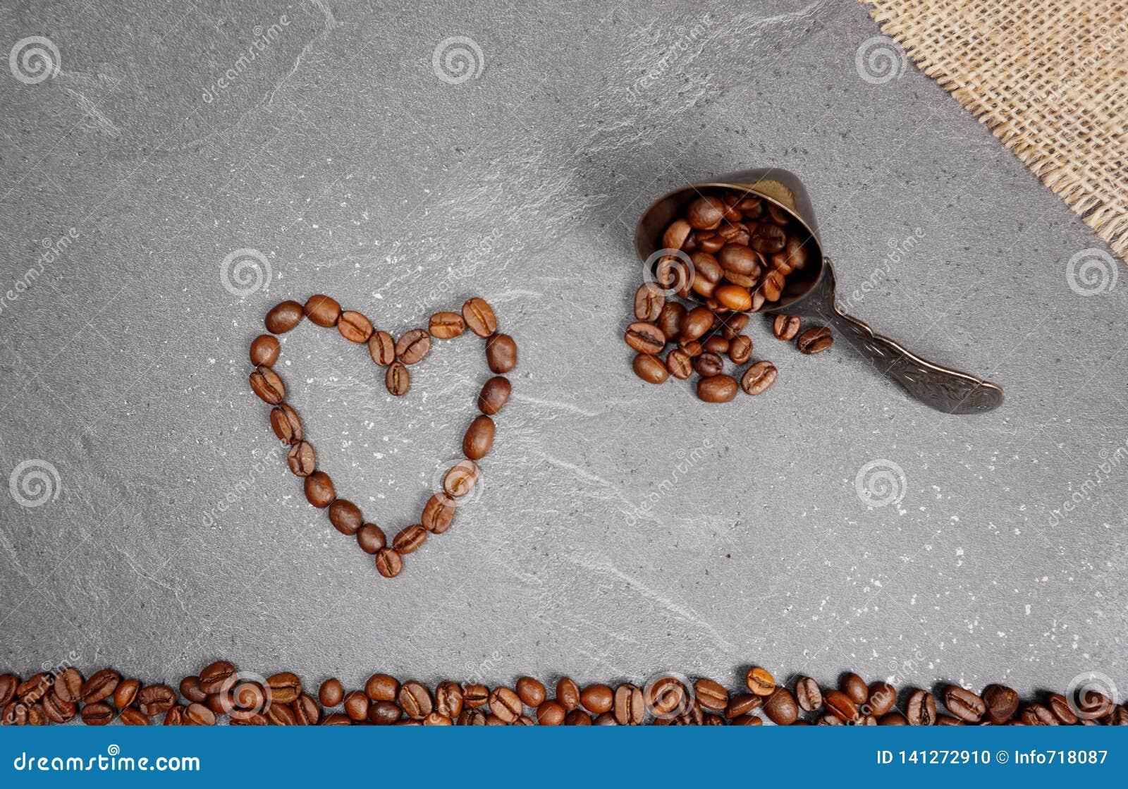 Serce od kawowych fasoli z burlap i łyżką przy popielatym kuchennym worktop tłem