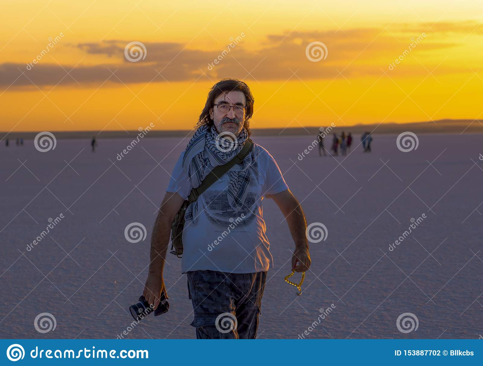 Sereflikochisar/ Turkey - July 07 2019: A silhouette of a Turkish man holds a camera in one hand and beads in other hand at Salt