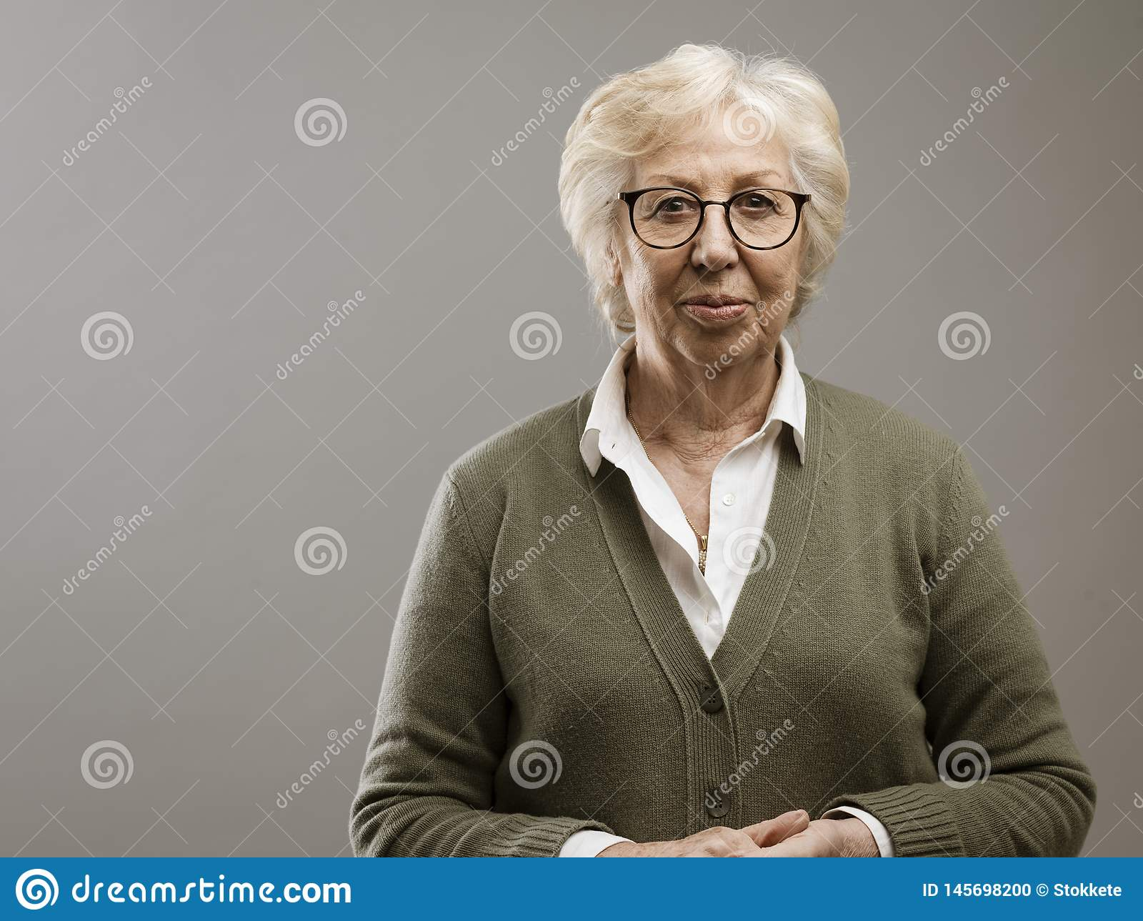 Serene old lady posing on gray background
