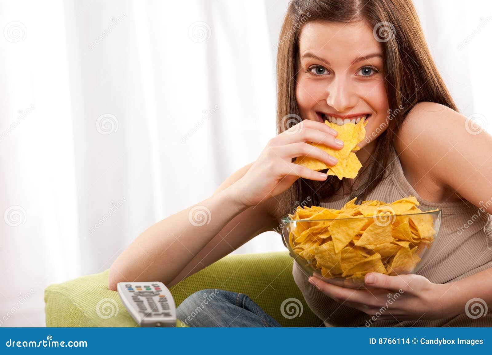 Serie del estudiante - mujer joven que come las patatas fritas