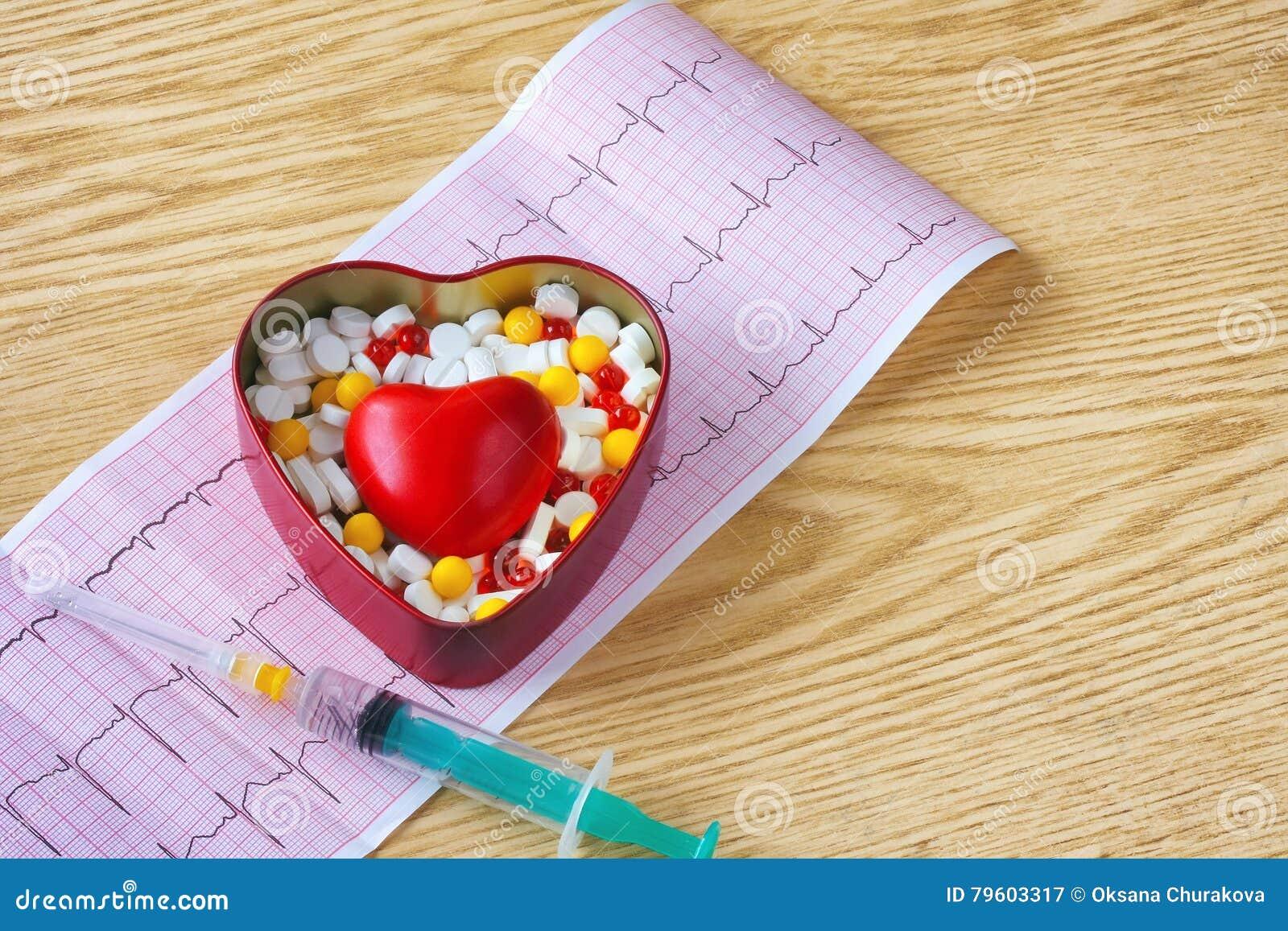 Seringa, cardiograma, caixa da tabuleta e coração vermelho