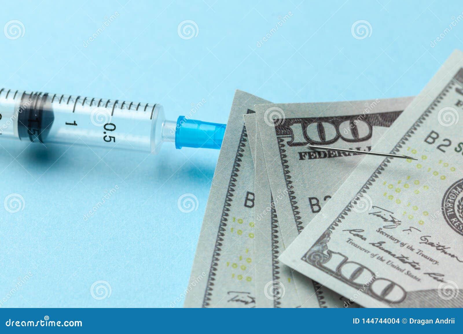 Seringue et dollars de papier goupill?s ? l aiguille sur le fond bleu Assurance-maladie ch?re