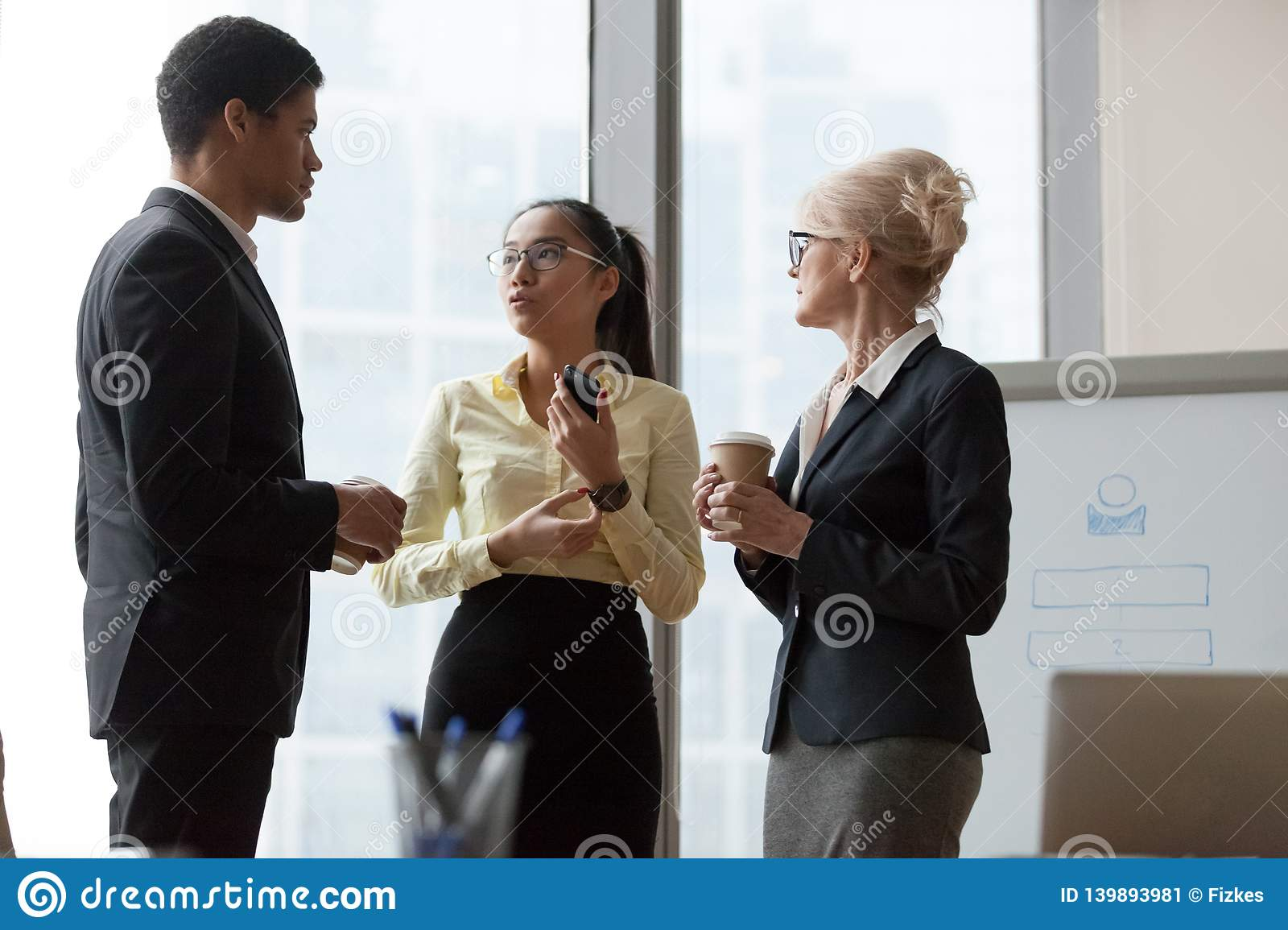 Serious african asian and caucasian colleagues talking at work break