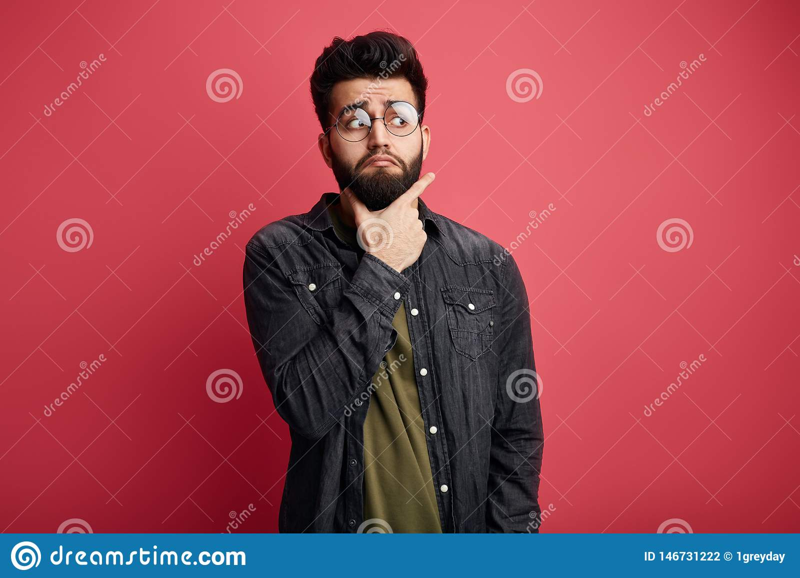 Serious attractive bearded stylish man touching chin and looking aside at camera