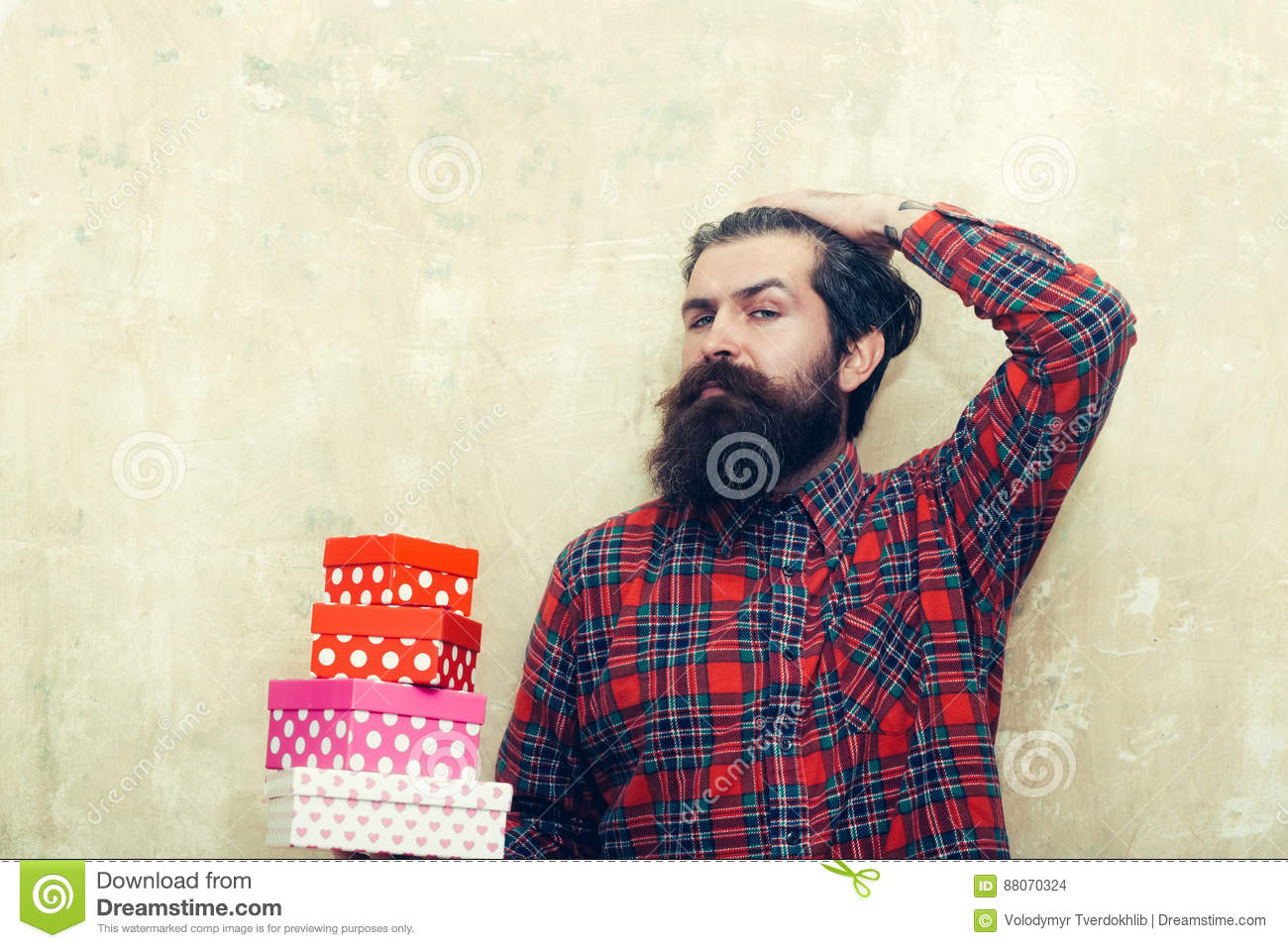 Serious bearded man holding colorful gift boxes stacked in hands