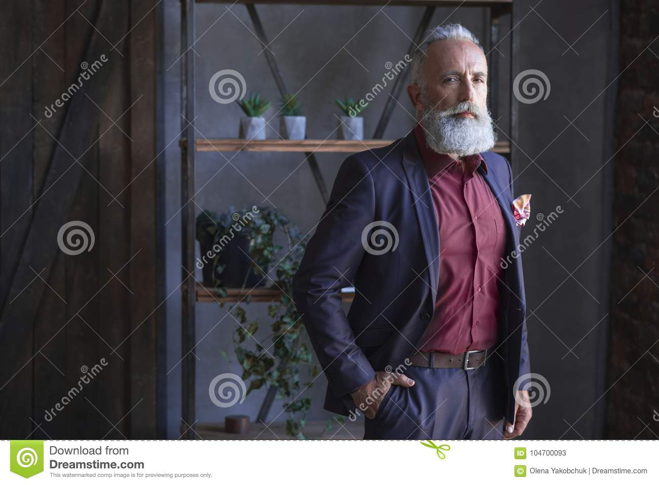Serious bearded retire situating in room