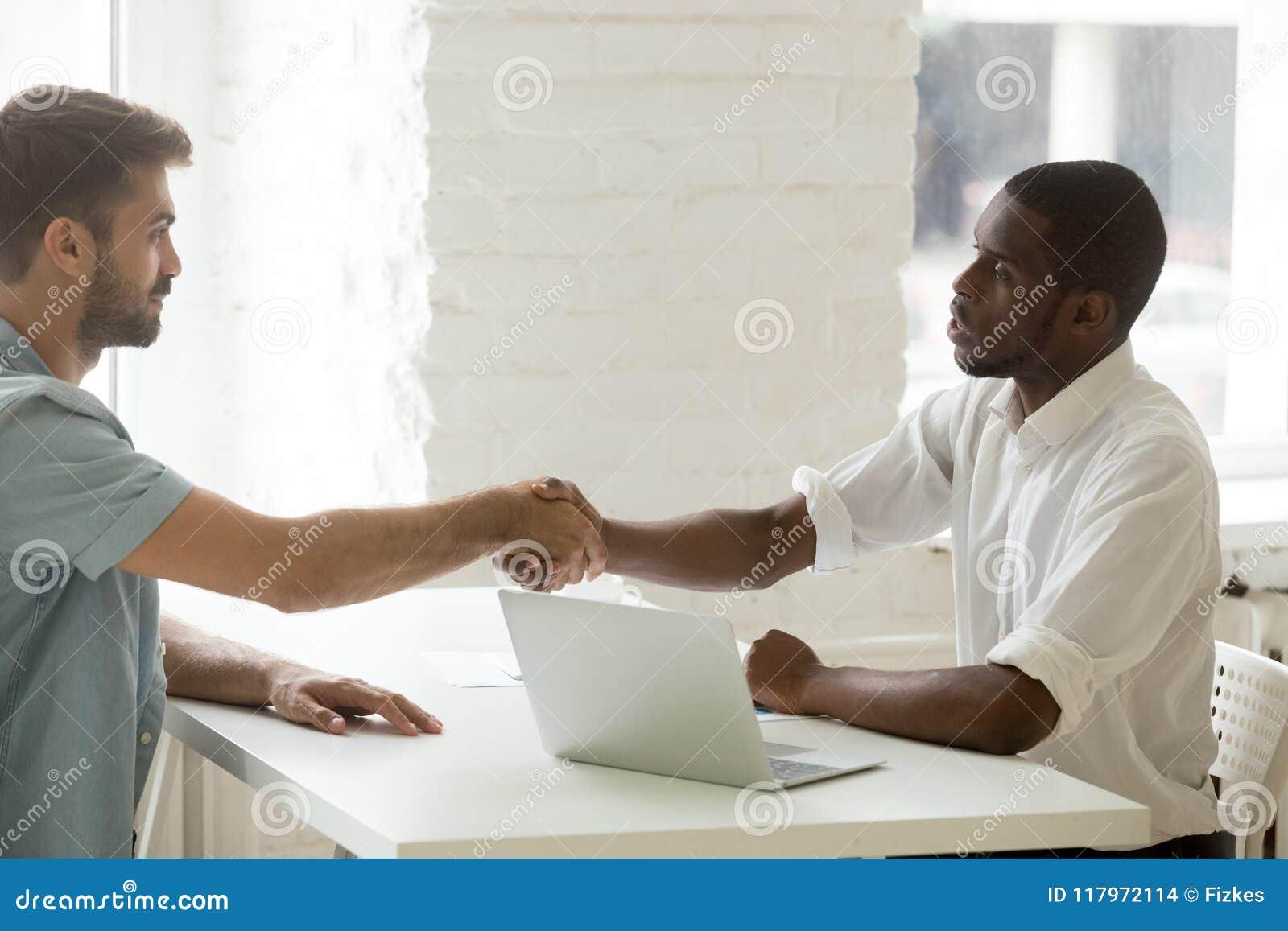 Serious Black Boss Greeting Caucasian Candidate With Handshake Stock