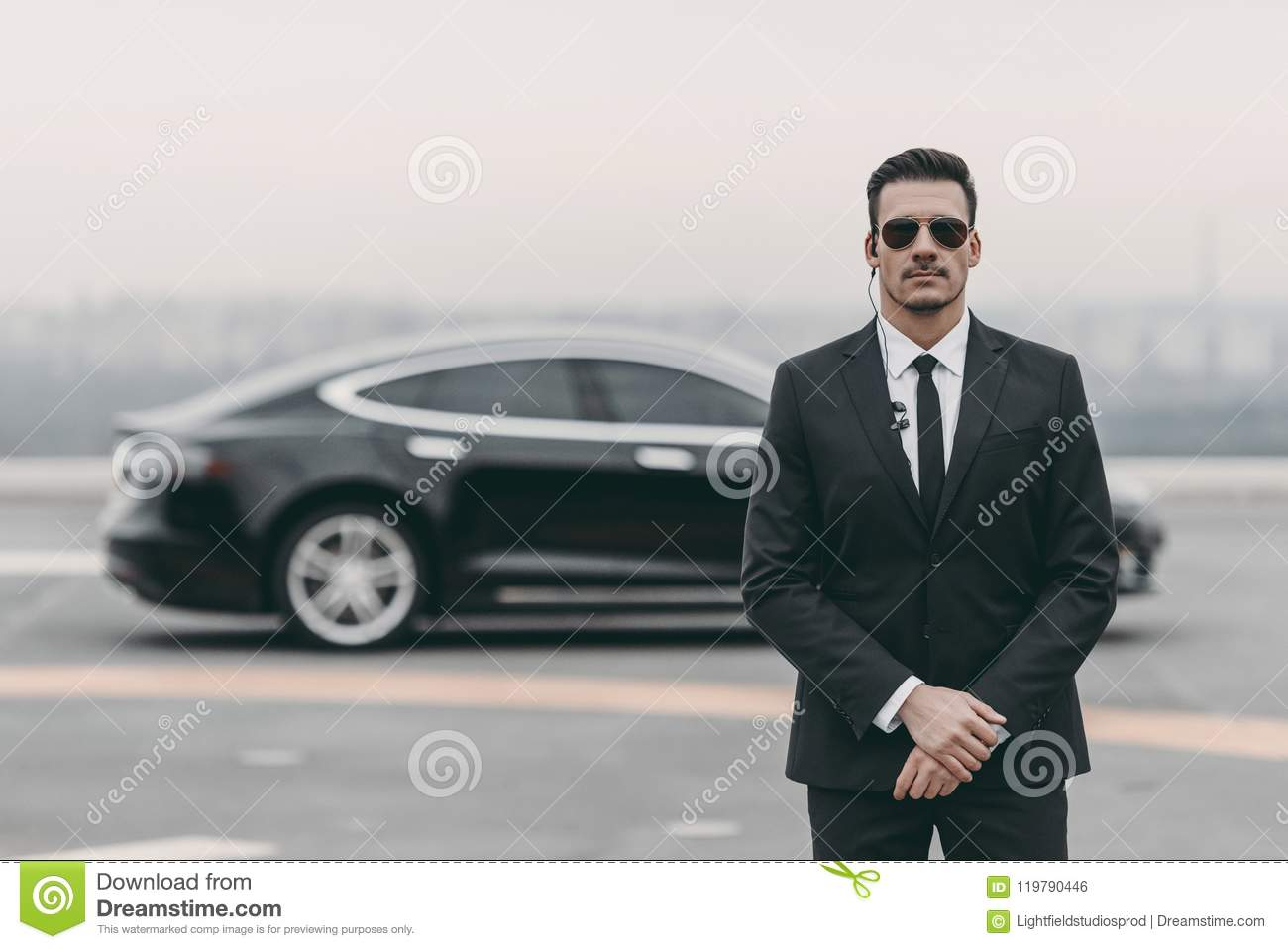 serious bodyguard standing with sunglasses and security earpiece
