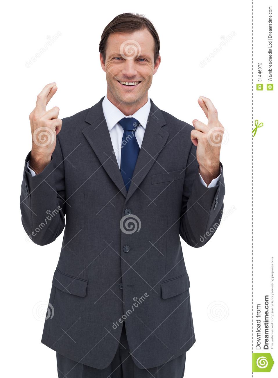 Serious businessman with fingers crossed