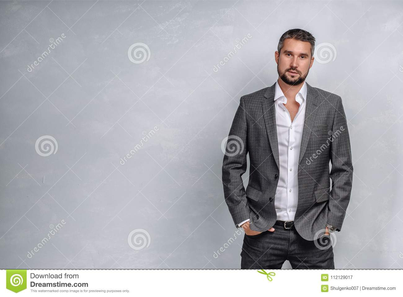 bf42d6829150 Serious CEO Stands On The Background Of A Clean Wall. Businessman In ...