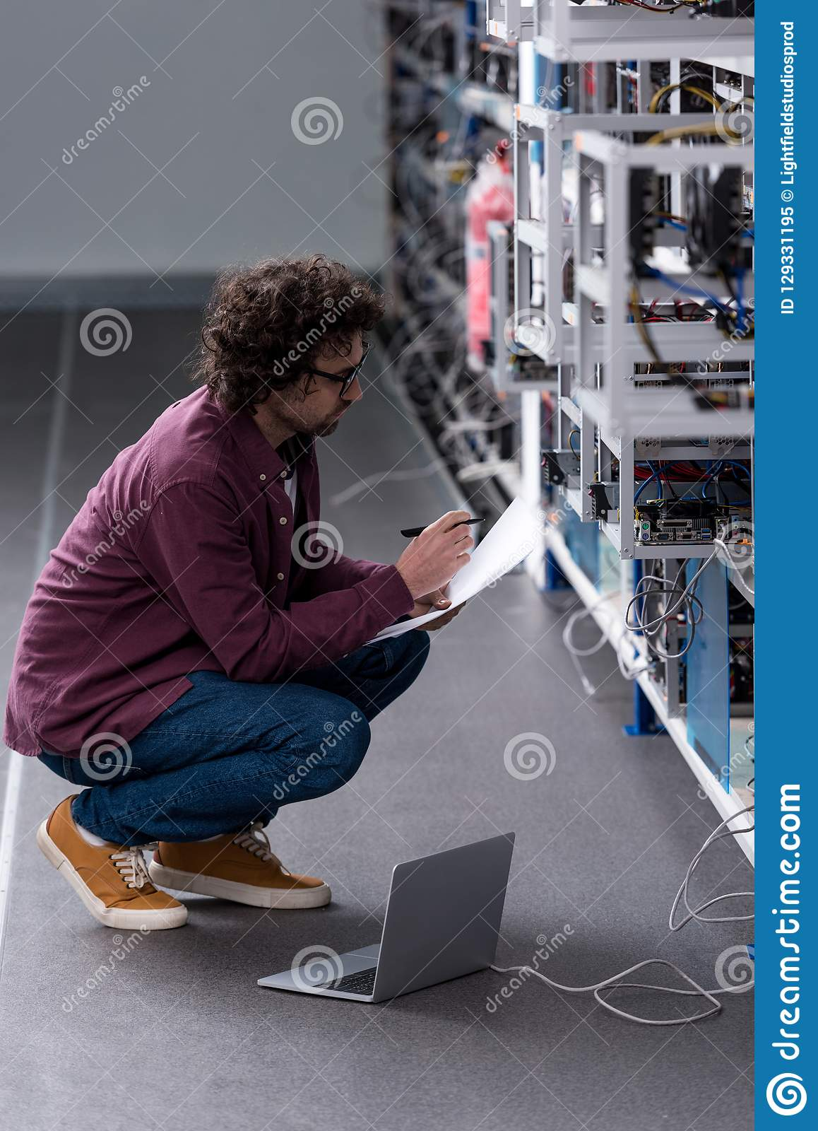 Serious computer engineer working while sitting on floor at cryptocurrency mining farm royalty free stock photo