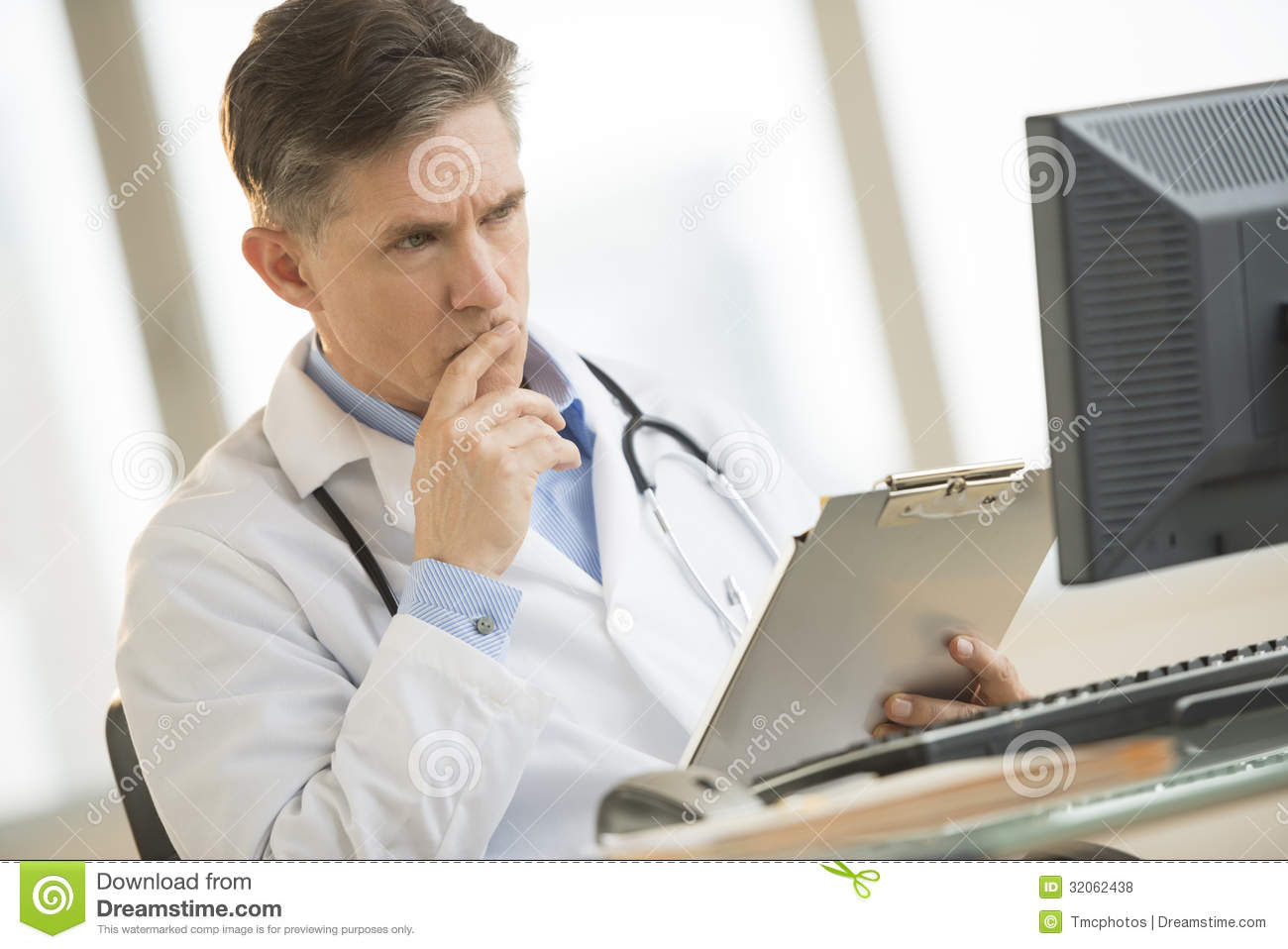 Serious Doctor Looking At Computer While Holding Clipboard