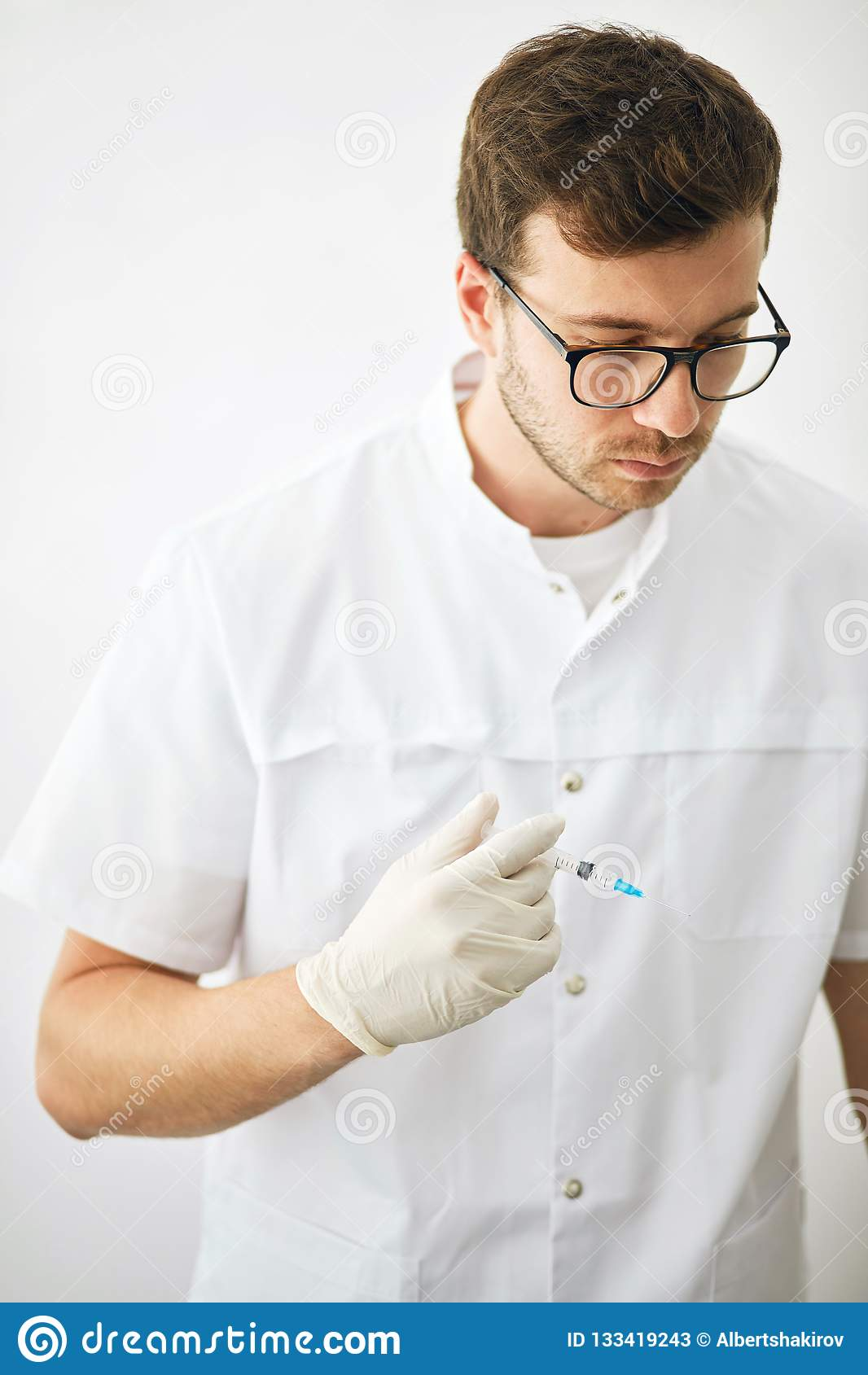 Serious doctor with medicine vaccination equipment with needle.