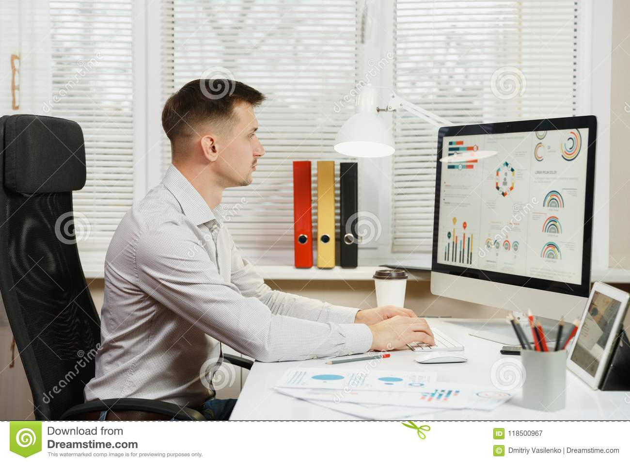 Serious and engrossed business man in shirt sitting at the desk, working at computer with modern monitor. Manager or worker.