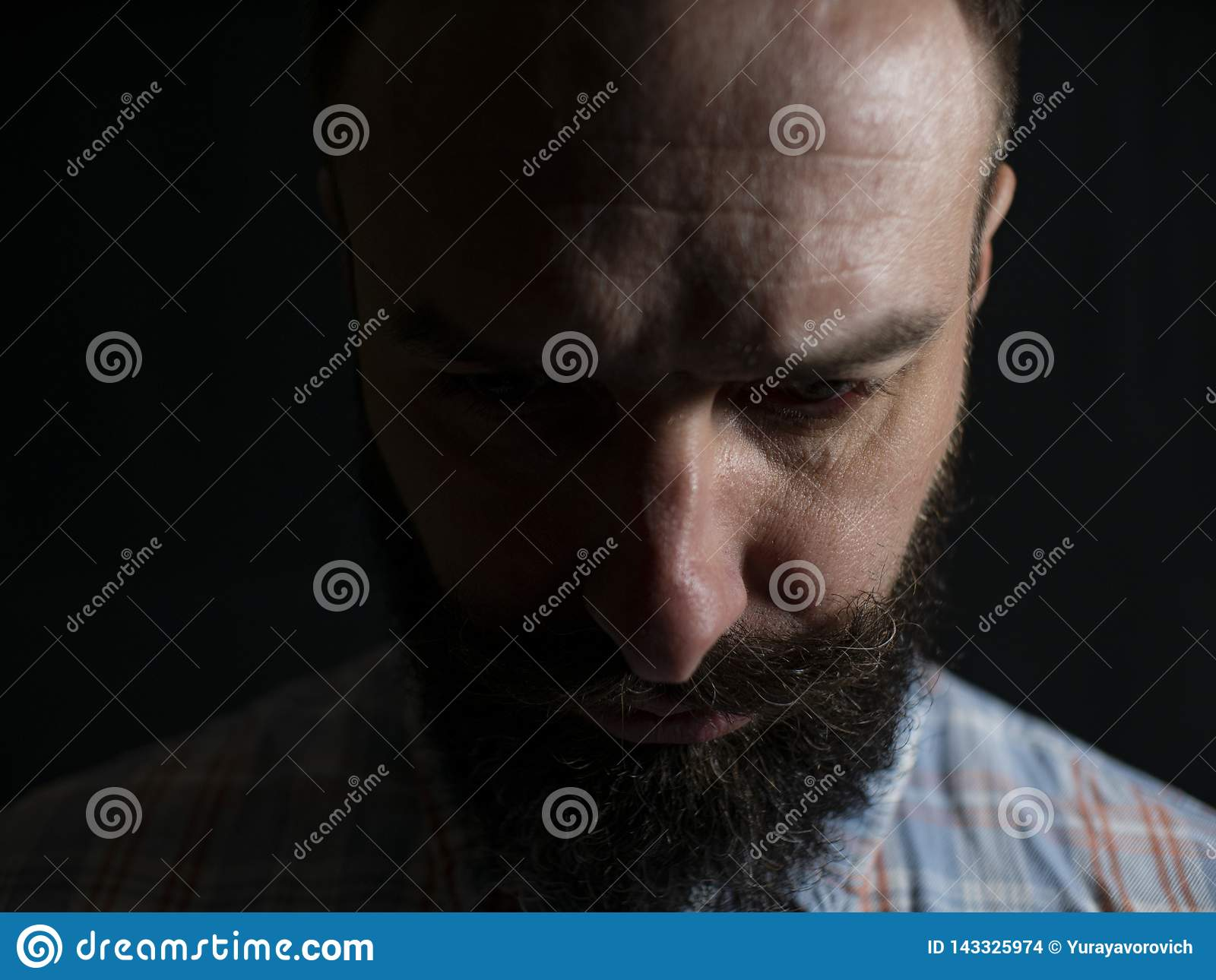 Serious face of a stylish man with a beard and mustache close-up looking to the bottom on a black background