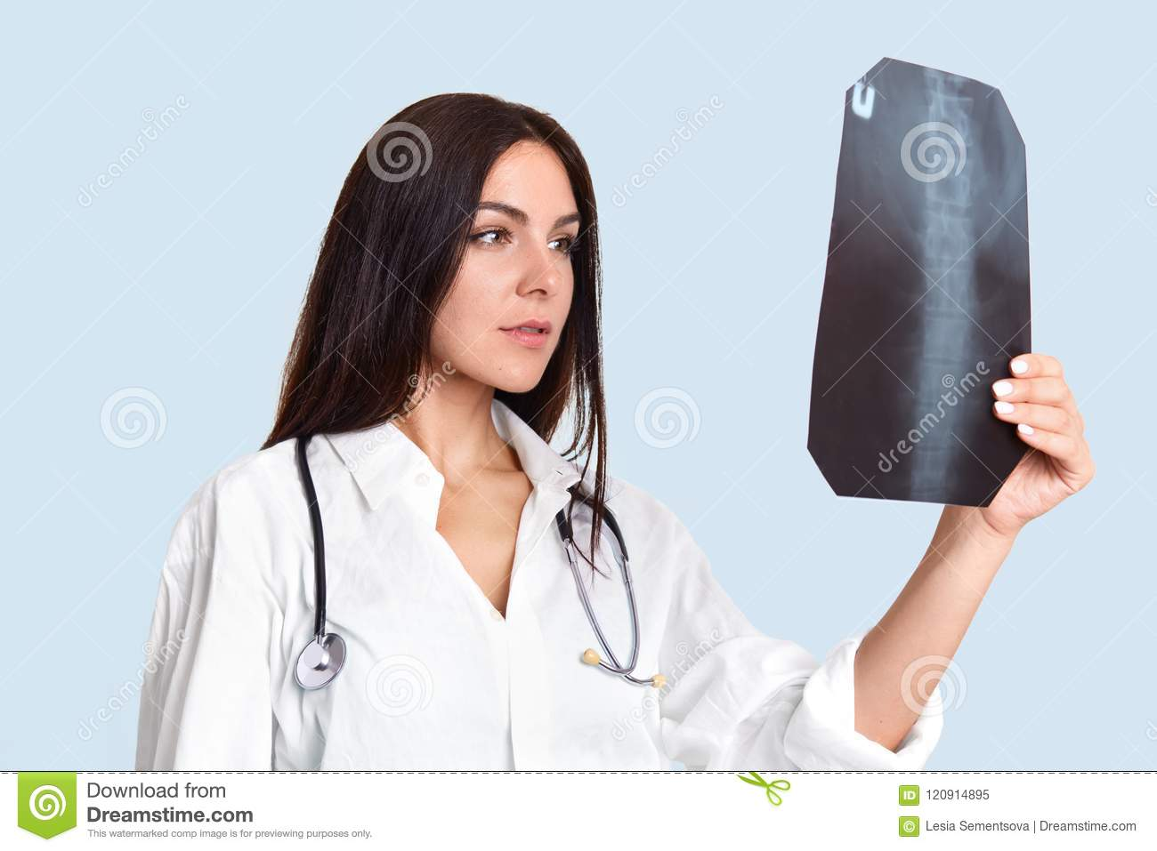 Serious Female Doctor Looks Attentively At X Ray, Examines People`s ...