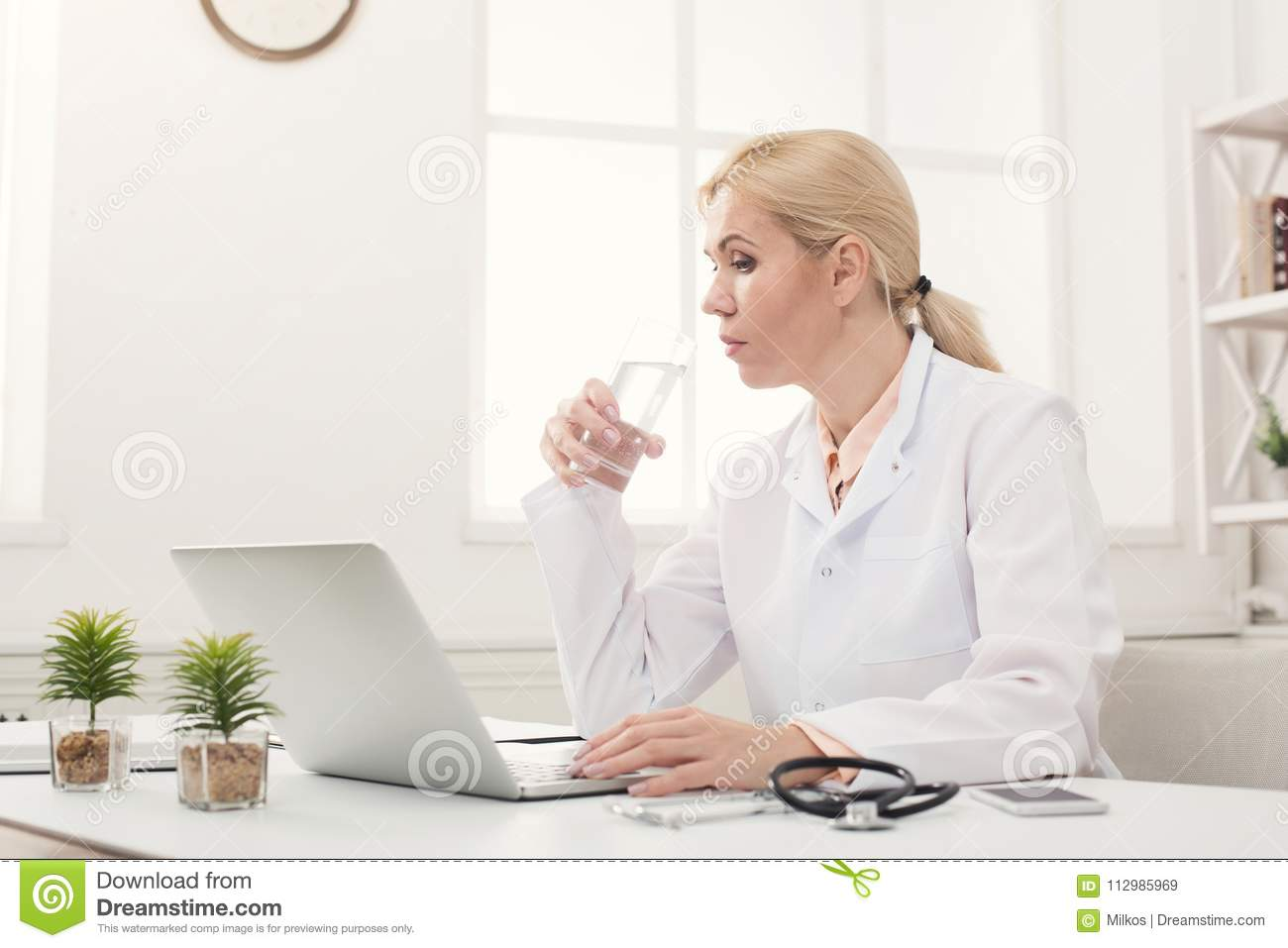 Serious female doctor typing on laptop