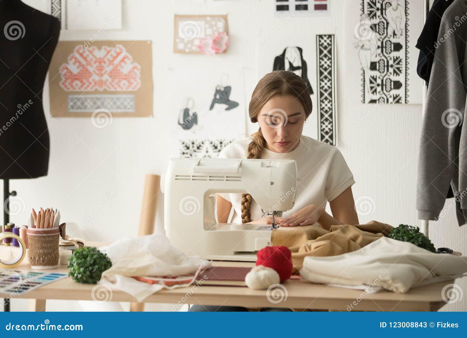 Clothing Design Studio | Female Tailor Stitching On Sewing Machine In Design Studio Stock