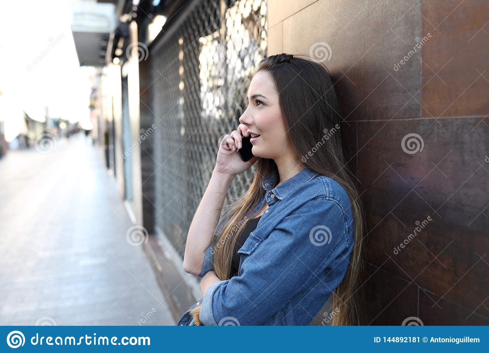 Serious girl profile talking on phone in the street