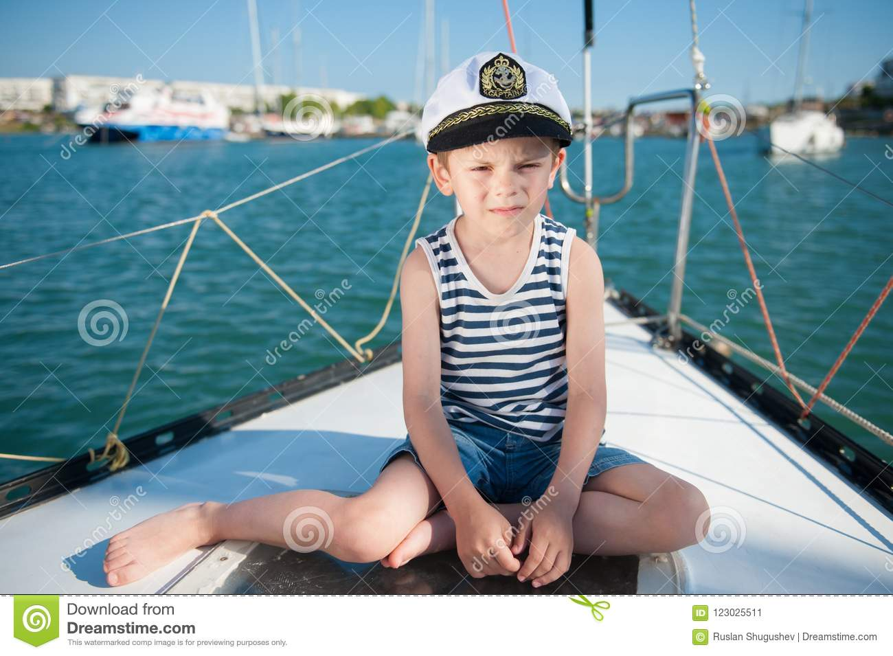 Serious Kid In Captain Hat Sitting On Luxury Yacht Board In